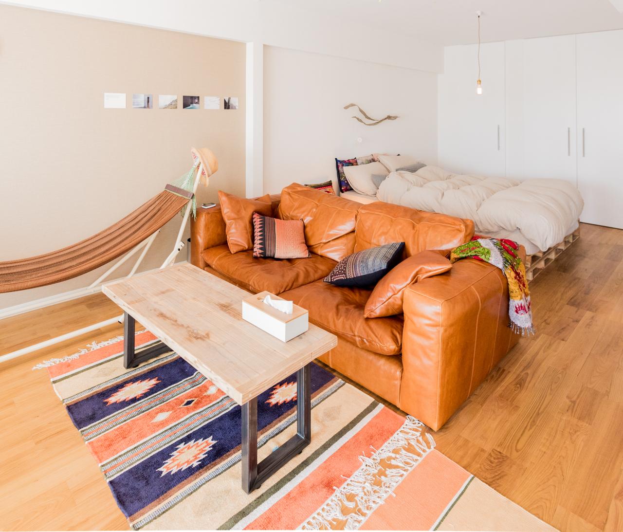 もともとは奥のベッドがある空間と、手前のソファとテーブルがあるスペースは別の空間だった。リノベされて広々としたワンルームに。
