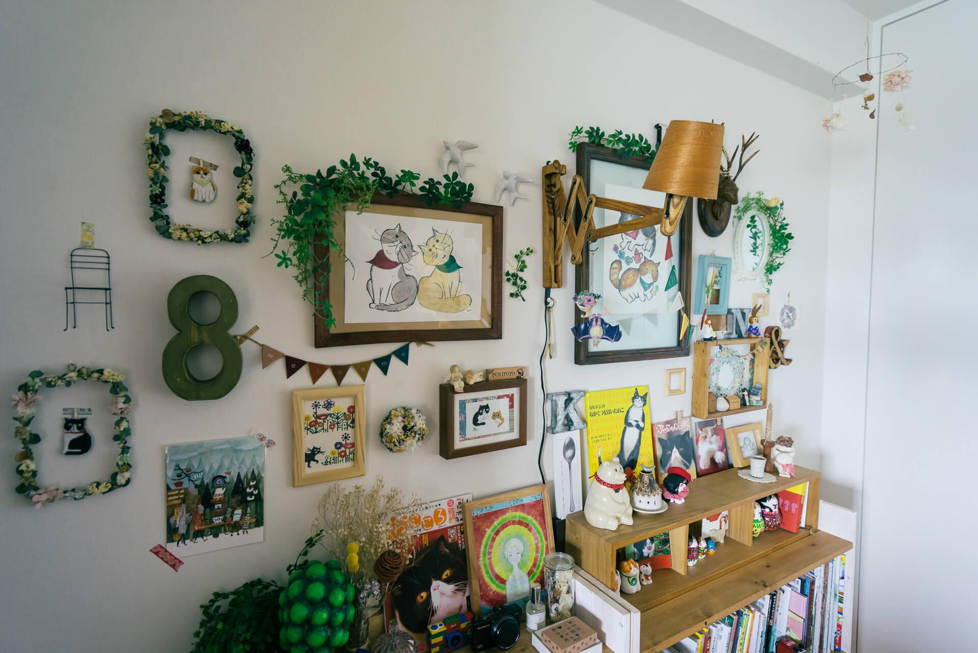 猫グッズが楽しく飾られたコーナー。右側の大きな絵はなっつ。さんご自身が、左側はお友達が描いてくれたものだそう。