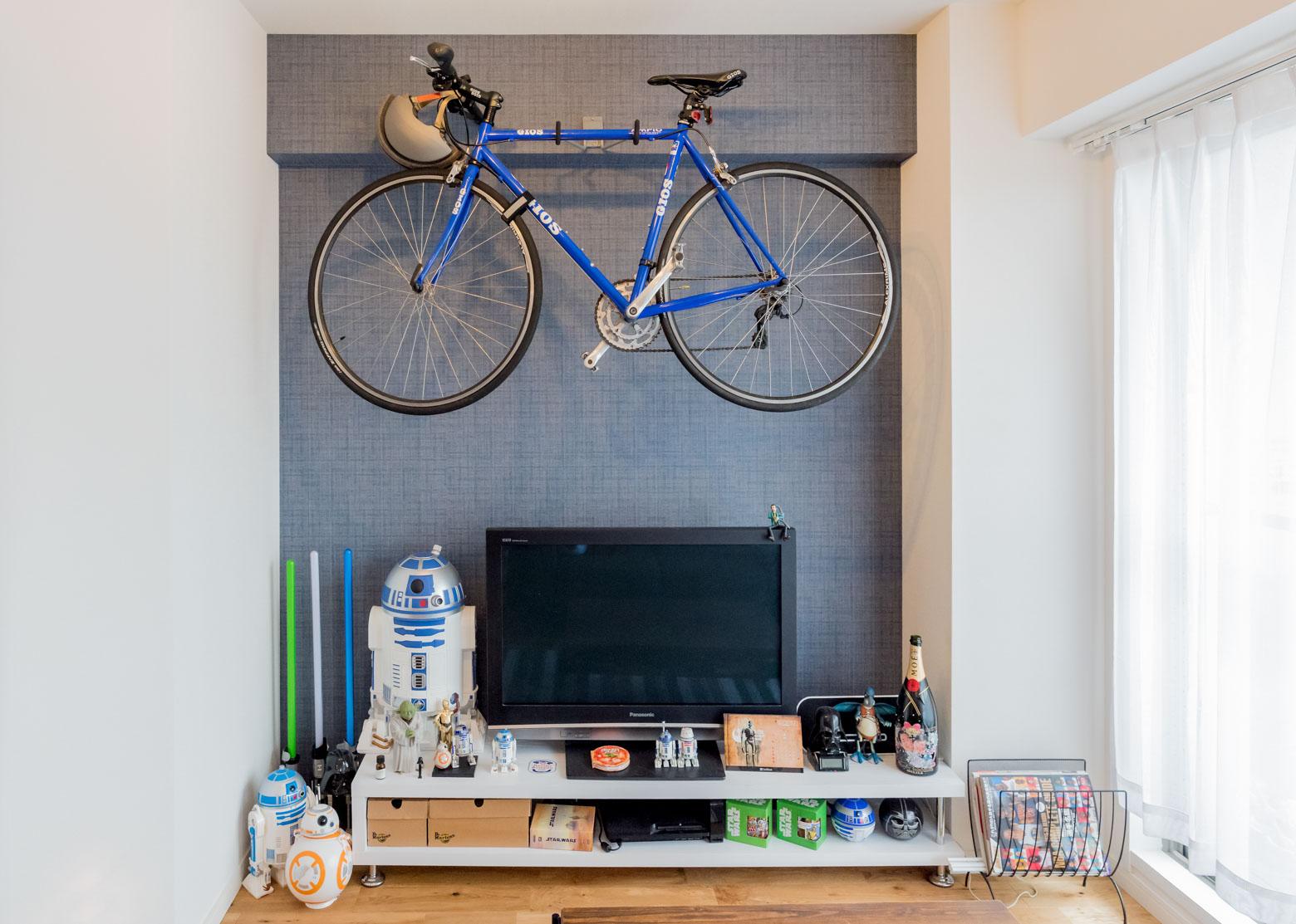 アクセントクロスのリビングの壁には自転車が。かっこいい。テレビ台に並べられたものたちが気になると思うが、これについても後述。