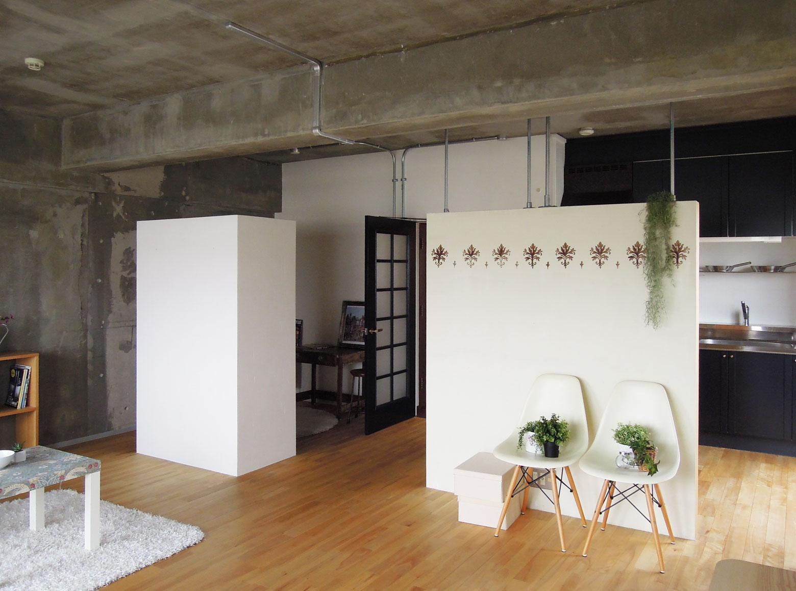 壁、天井はコンクリート剥き出し。手前の模様の入った壁は住まい公社主催のワークショップで仕上げられた