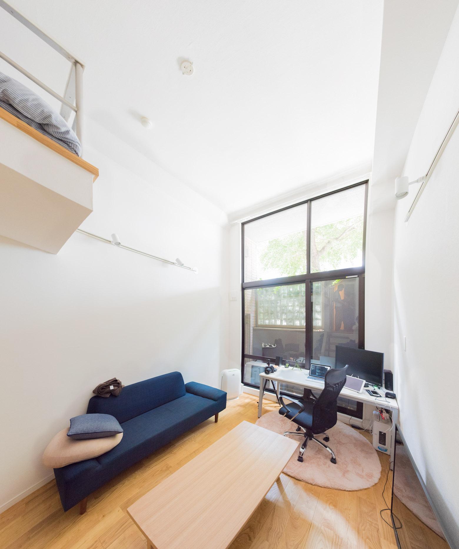 玄関からキッチンなどを通り抜けて、数段階段を下がった空間が居室。下1/3は半地下ということになるが、一面がすべて窓で天井が高いのでとても明るい「眩しいぐらいですよ」と中村さん。