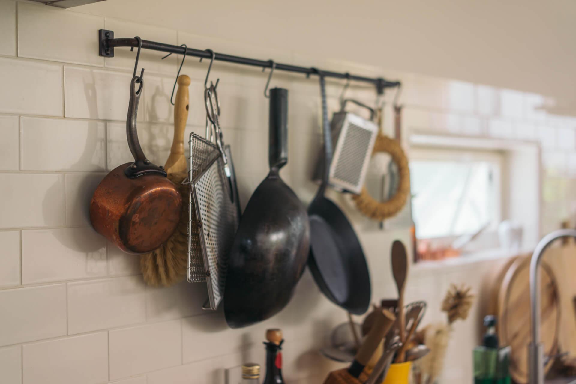 壁面はキッチンルールを見せて収納。このアイアンのハンガーレールも、タイルの目地にぴったり合うサイズで、前編でご紹介した鉄屋さんが作ってくれています。