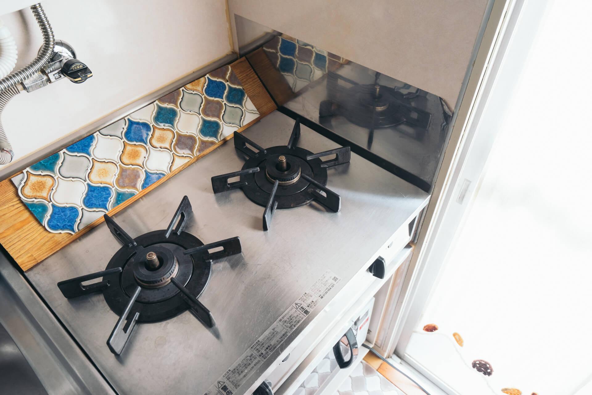 """シンプルなガス台の奥は、耐熱の""""貼るだけタイル""""で隙間をふさいで。こうすると、ガス台まわりの掃除も簡単になります。"""