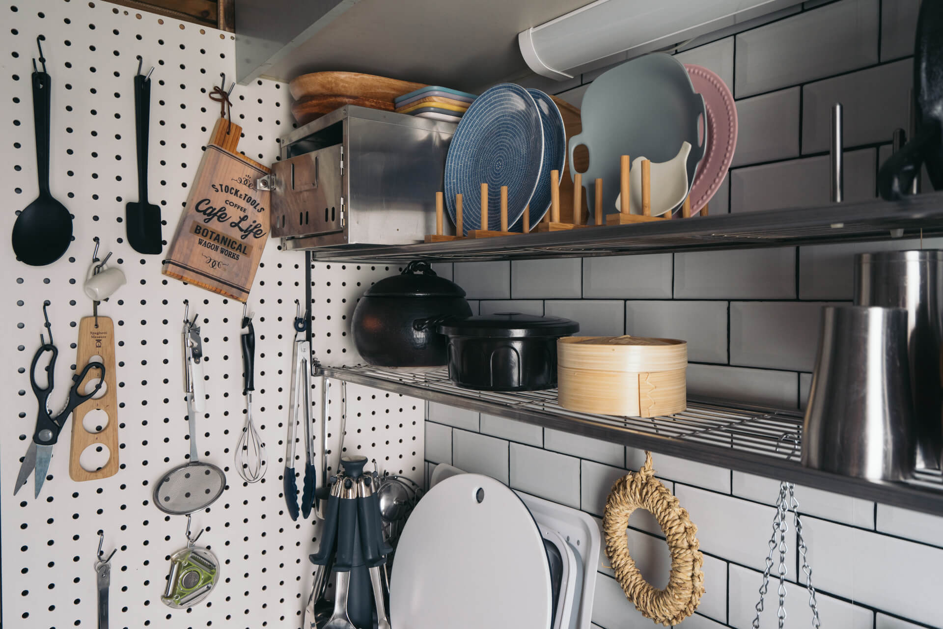 こちらはシンク側。有孔ボードを冷蔵庫の側面に吊り下げ、キッチンツールもすべてさっと手がとどく位置に。水切り棚には特にお気に入りの器が並びます。