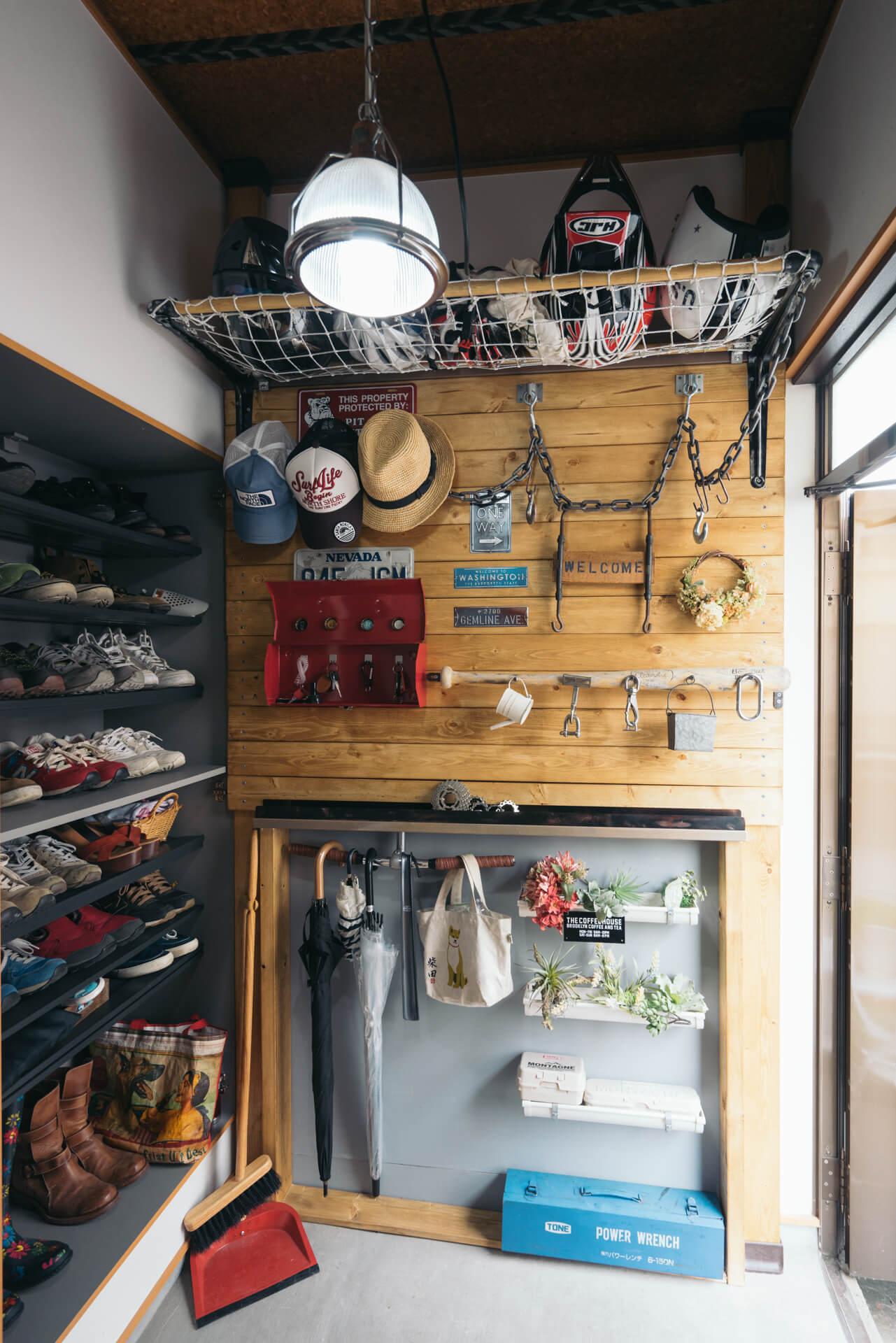 玄関にもお手製の板壁。よく見ると自転車のハンドル部分やバットが使われ、遊び心が。