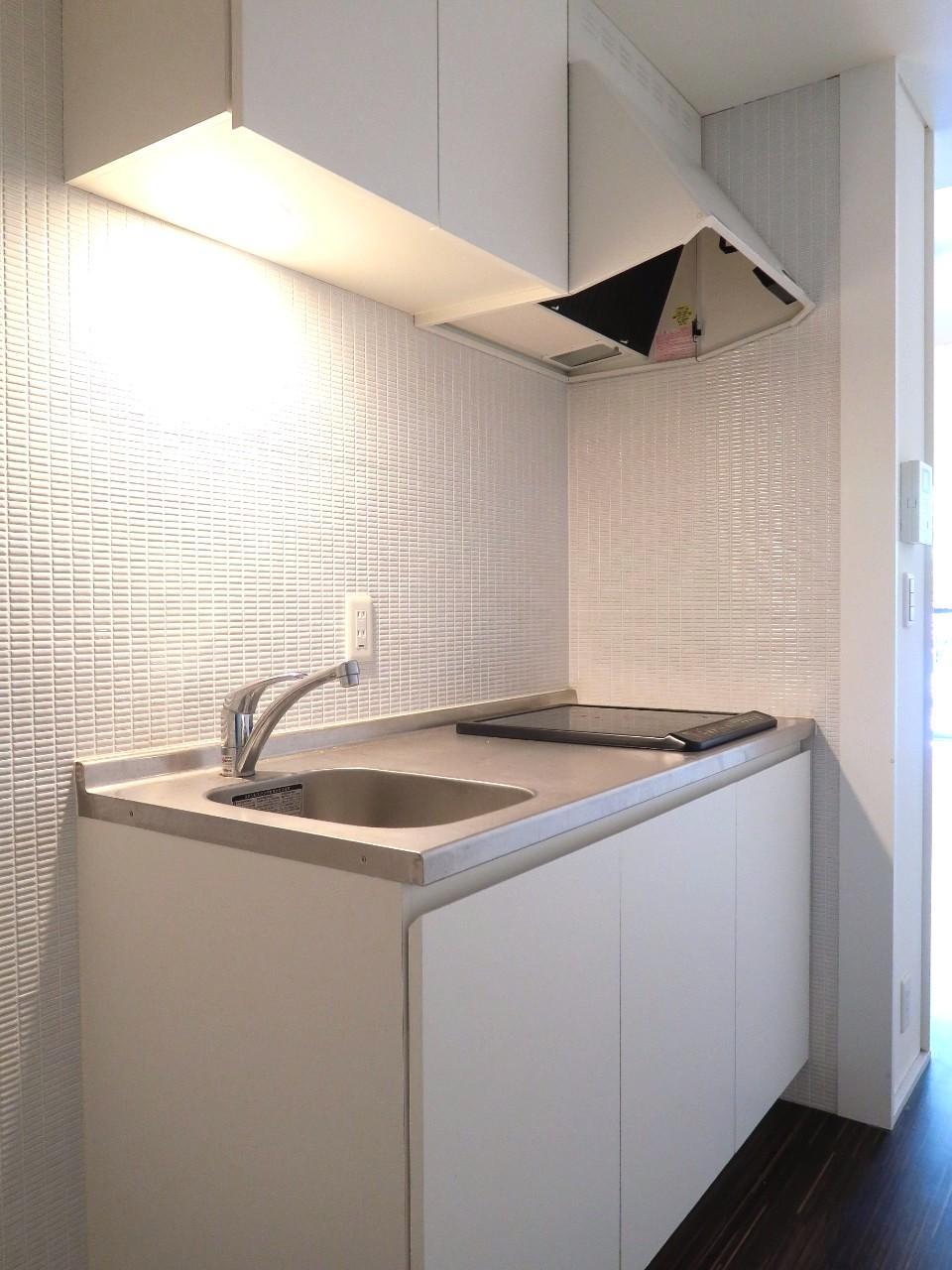 白の細長いタイルが可愛らしいキッチンは2口IH仕様。