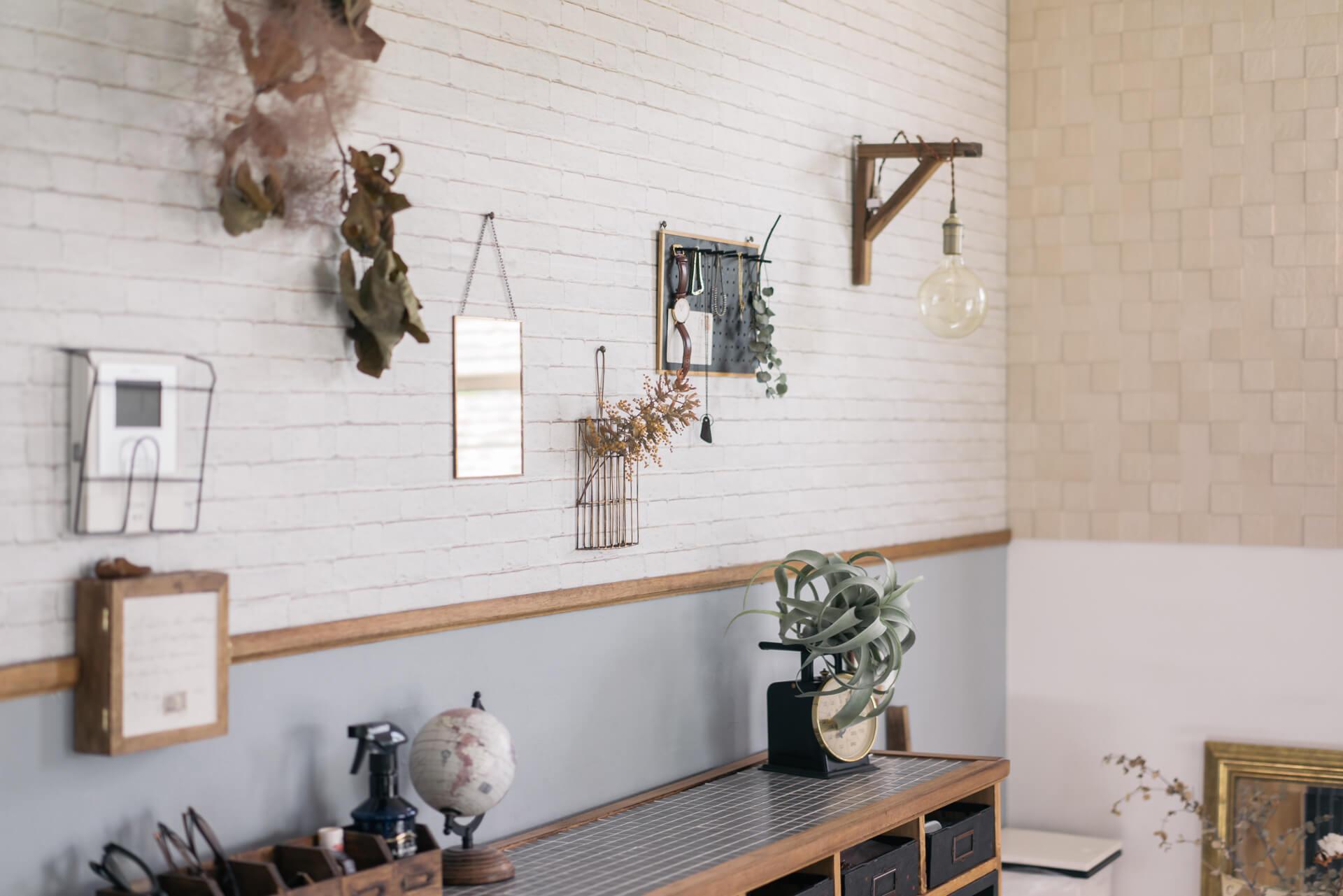 レンガ風の壁紙を貼ったり、色を塗ったり。楽しい雑貨やグリーン、ドライフラワーが絶妙なバランスで飾られています。
