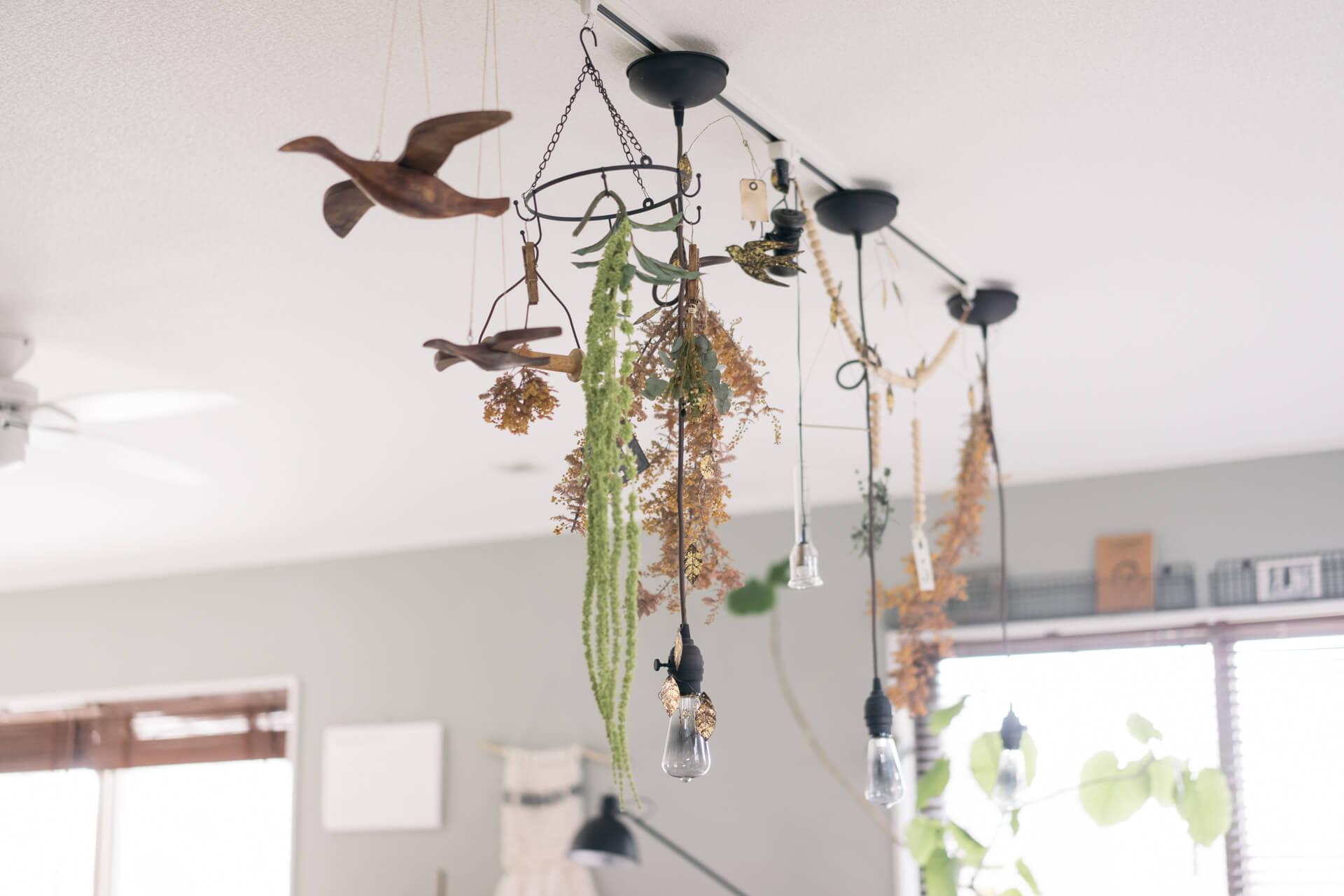 テーブル上のライティングレールには、照明だけでなく、ドライフラワーや鳥のオブジェを飾って楽しい雰囲気に。こういう飾り方、真似したい!