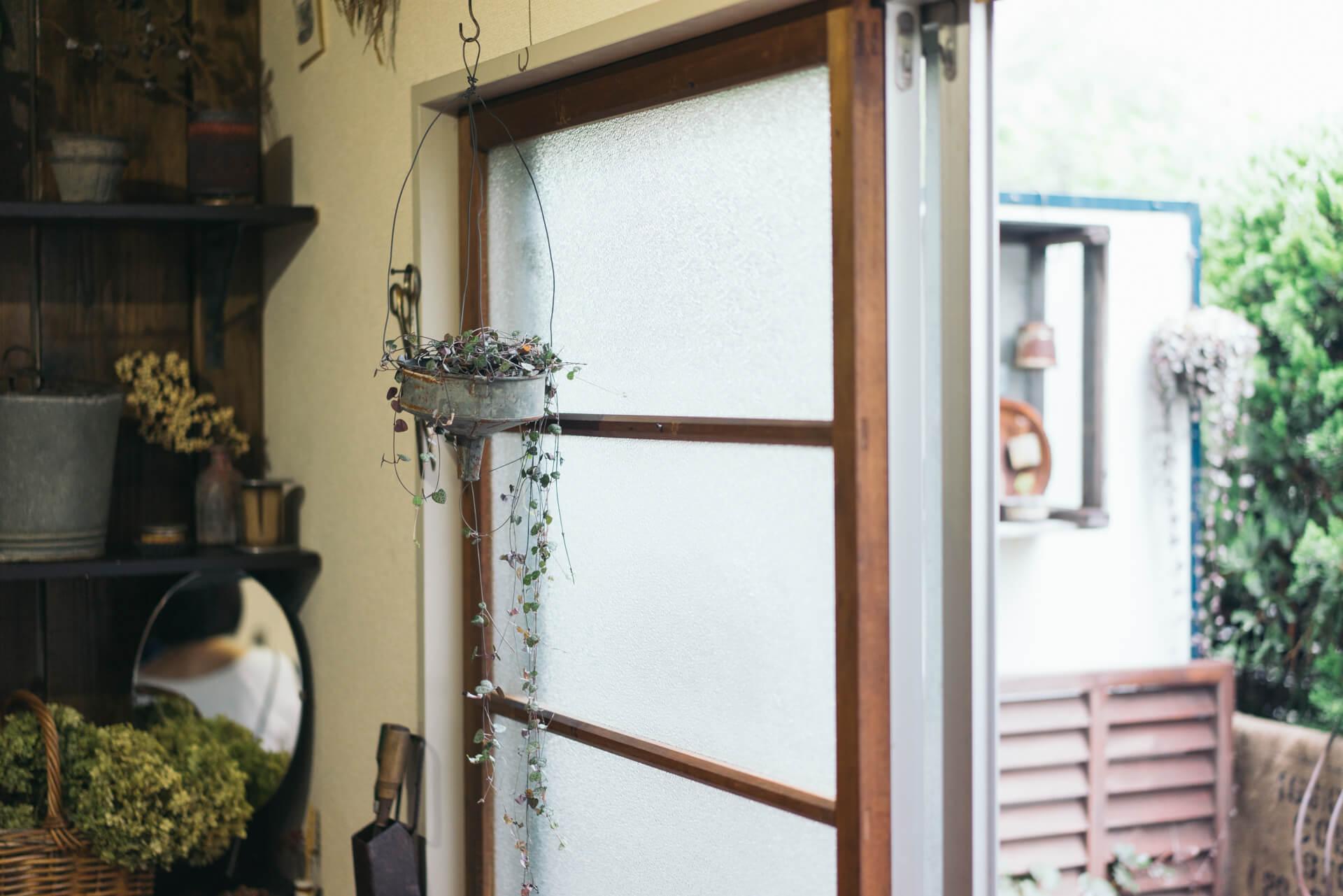 窓際には、カーテンの代わりに古い木のドアを元々のアルミサッシを隠すように配置。下にはレンガを置いて高さを微調整しつつ、ベンチを手前に置くことで足元を固定しています。