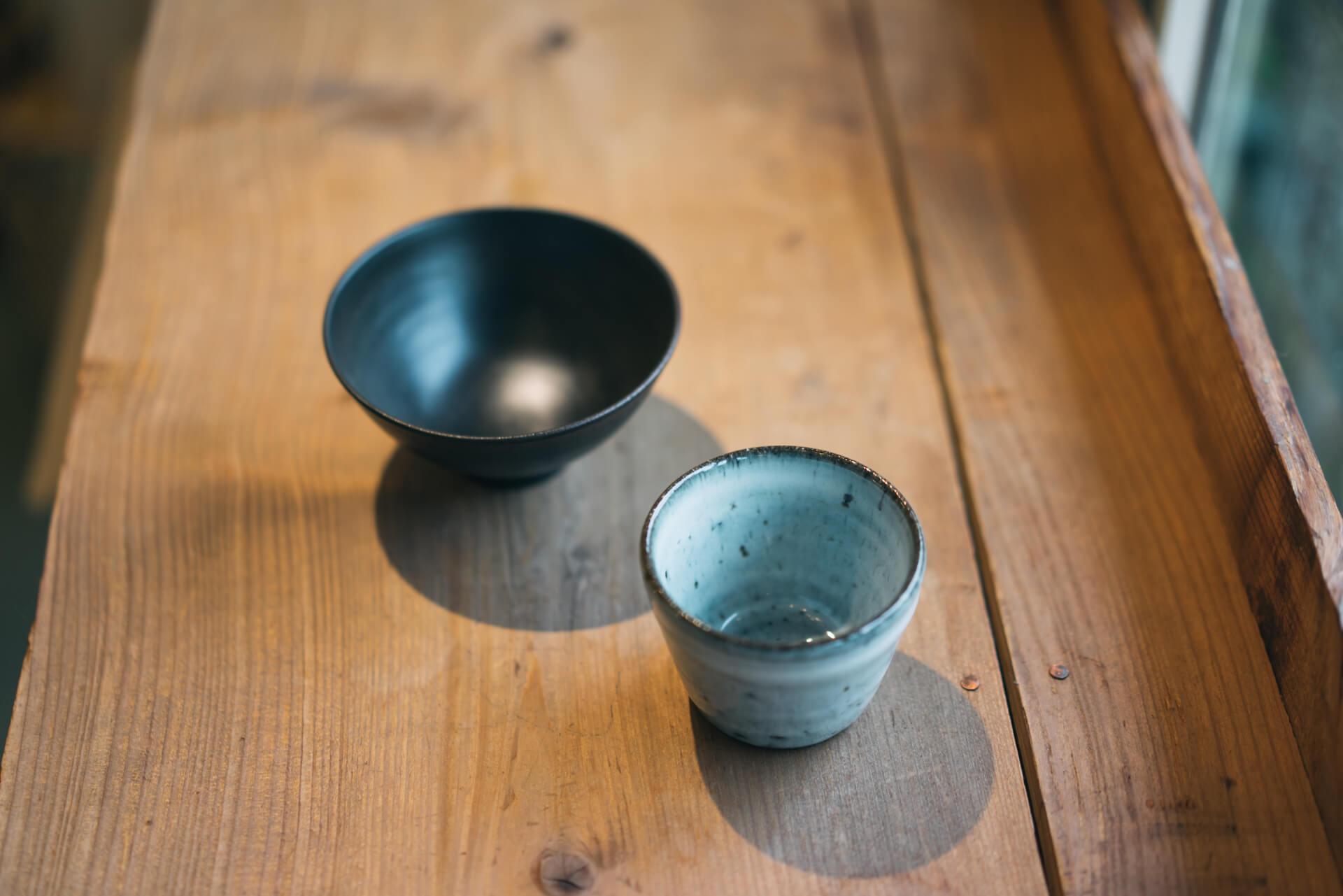 めし碗には、少しこだわったものを。小坂明(こさかあきら)さんの黒いめし碗(左)は、均一な厚みになるよう丹念に削り、漆を何度も塗り重ねながら焼き付けるなど、非常に凝った製法で作られるとっておきの逸品。