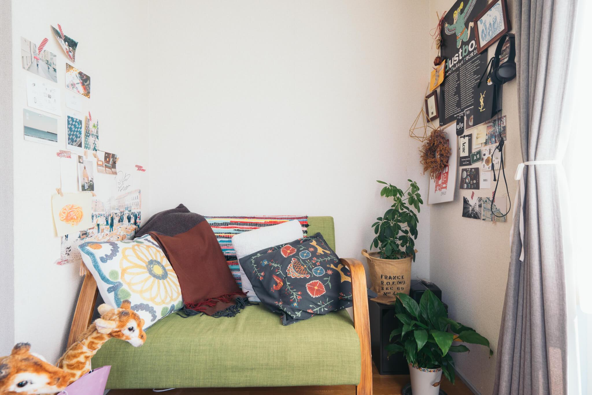 もとは押入れだった大きな収納の横にぽっかり、ソファのおさまるスペースが。好きで集めているというクッション、それに壁にたくさんのポストカードを飾って、とっても落ち着く空間に。ソファの肘置きはもっと白っぽい色だったのを、部屋に合わせて塗りました。