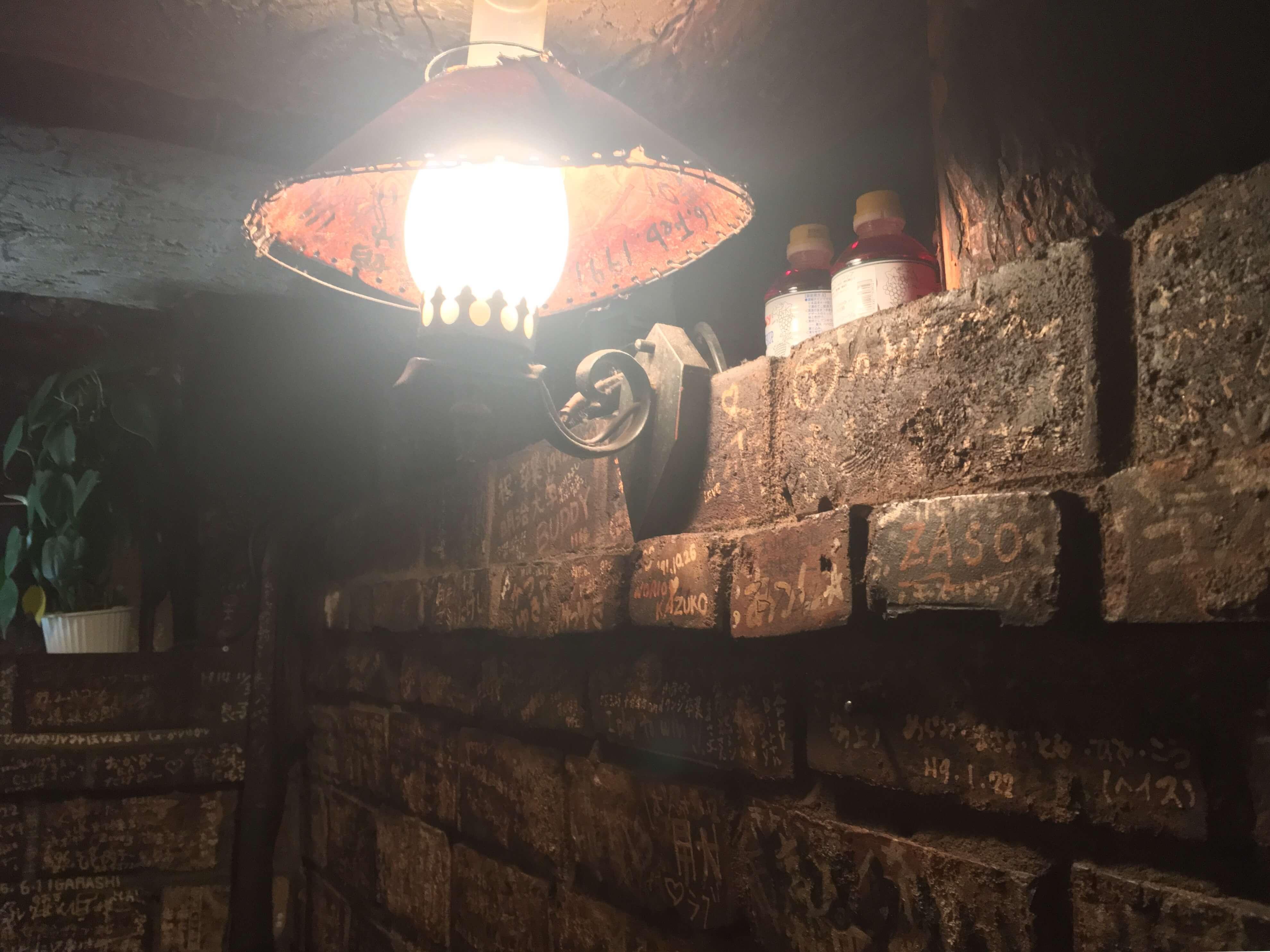 案内された席は半地下。薄暗い店内を見渡してみると壁や柱にビッシリと描かれたメッセージが!