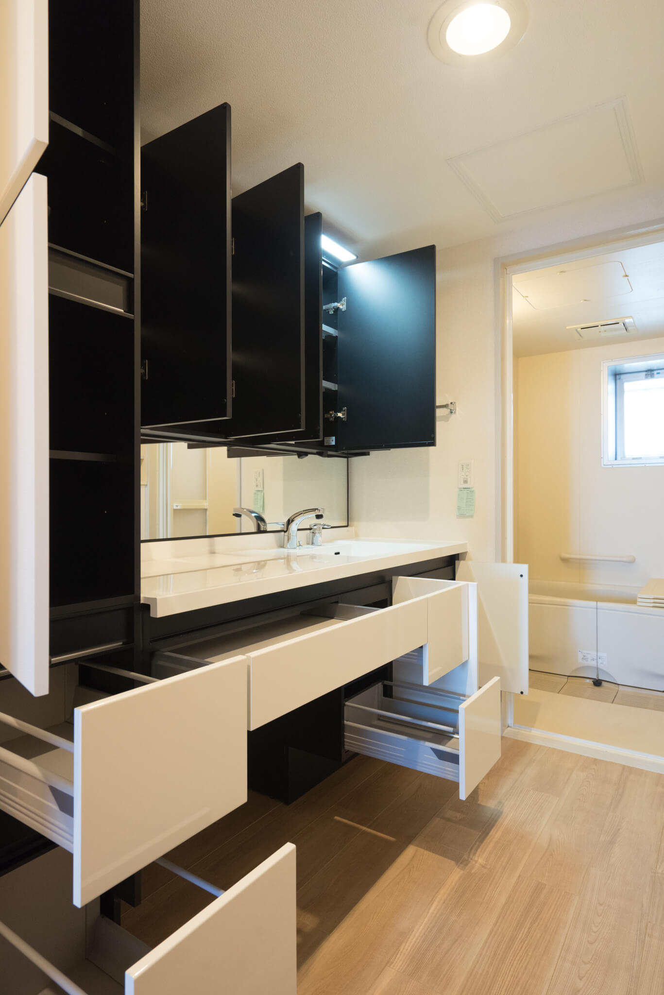 一番感動したのが、バスルームへと続く導線にある脱衣室、そして生活納戸の収納。広々の脱衣スペースにある大型洗面台には収納がこれでもかと。