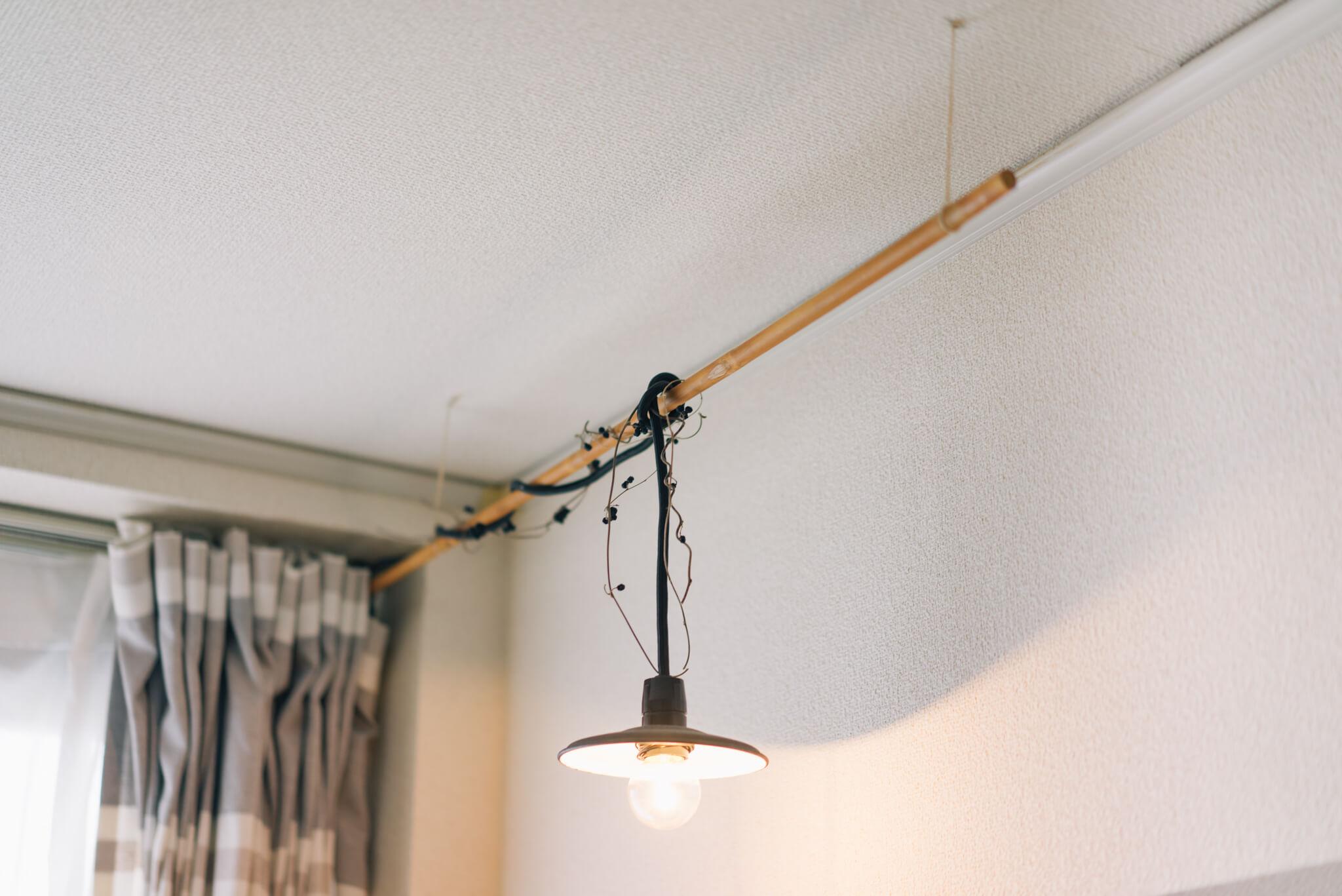 天井から丸棒を吊るし、そこにライトのコンセントをはわせる!丸棒を吊るす糸は、ホッチキスで天井に固定しているので穴は目立ちません。