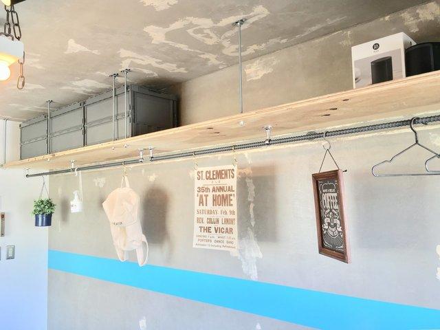 反対側の壁はこちら。天井近くの棚とハンガーパイプがずらっと。こういうお部屋、憧れだな。