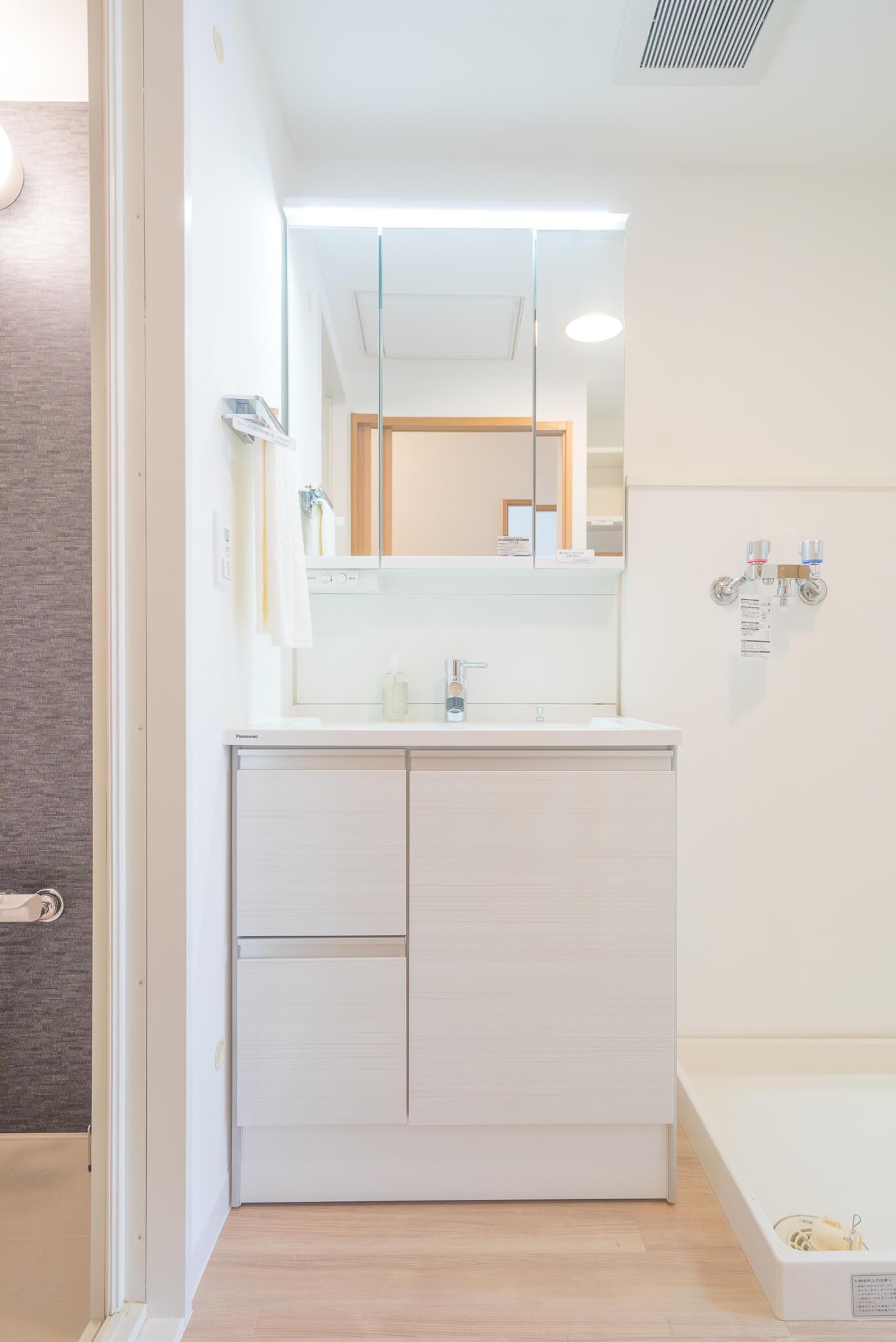シンプルなデザインが嬉しい洗面台は、タオル掛けの上に小物が置けるように考えられていたり、鏡の裏が大容量の収納になっていたり、機能面も十分。