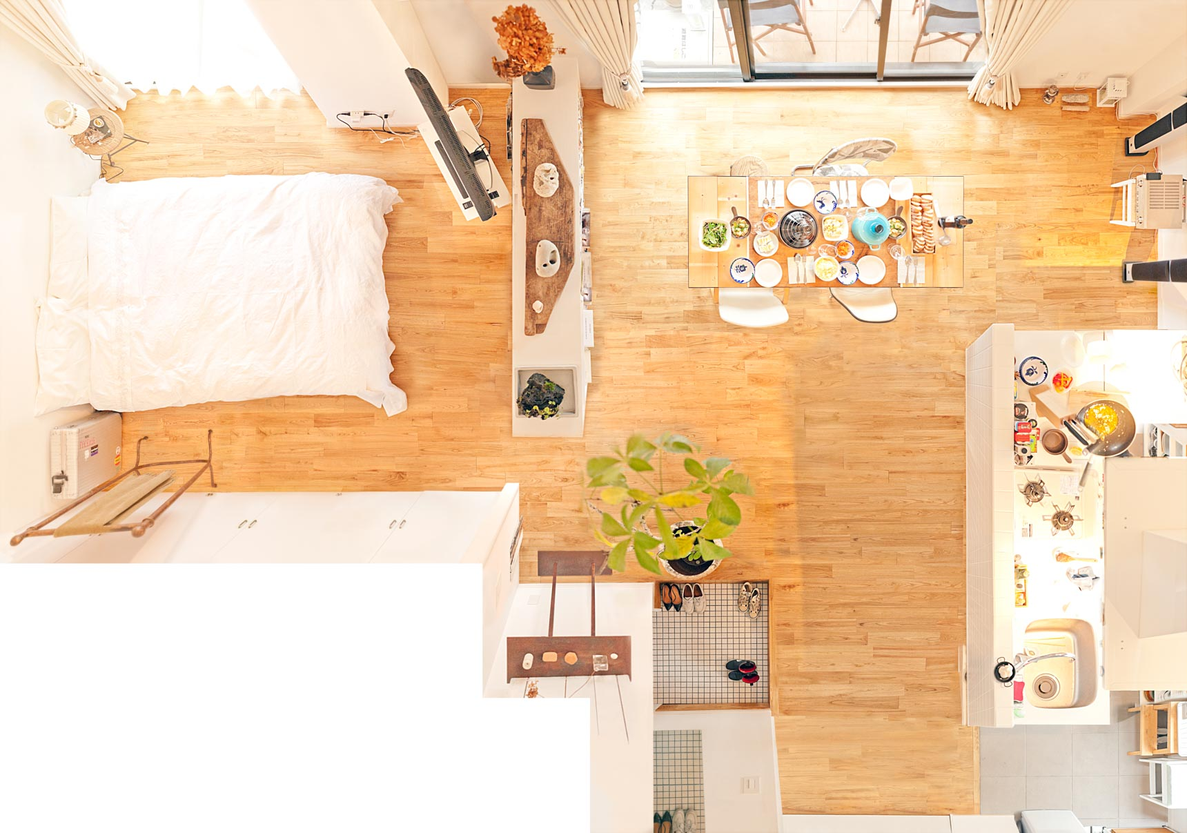 石井さんご夫婦のお部屋。アイランドキッチンを中心に、手料理を楽しむダイニングスペースはゆったり。テレビは、ベッドから見える位置へ。