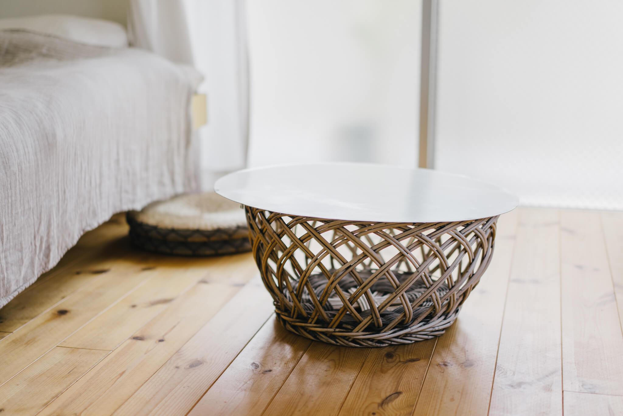無垢の床にもぴったりの、丸いローテーブル。よく見ると、銭湯などで見かける古い脱衣かごが使われていました。