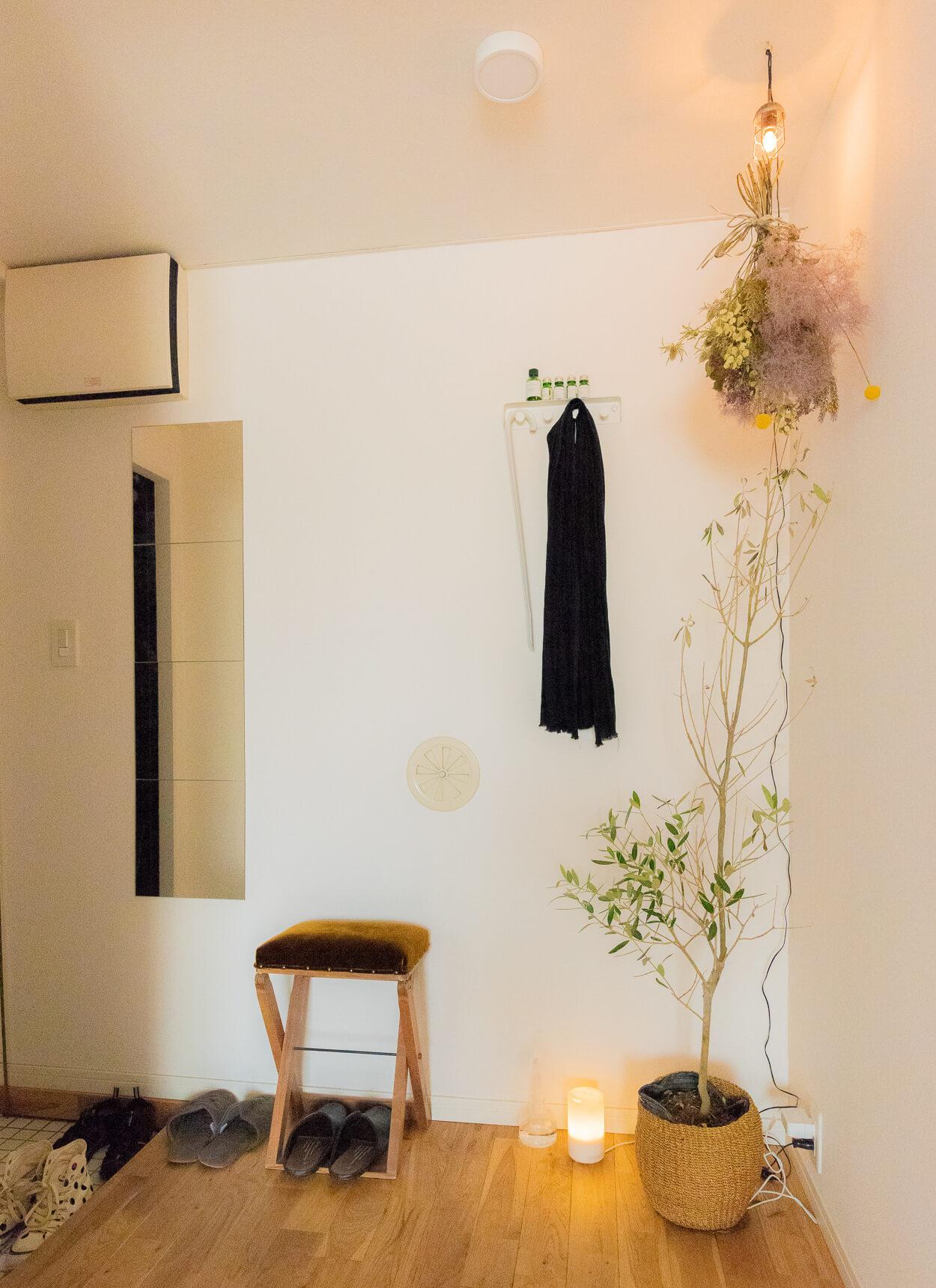 キッチンからぐるりと後ろを向いて玄関方向を見る。グリーンと照明、そしてかわいらしいスツール。