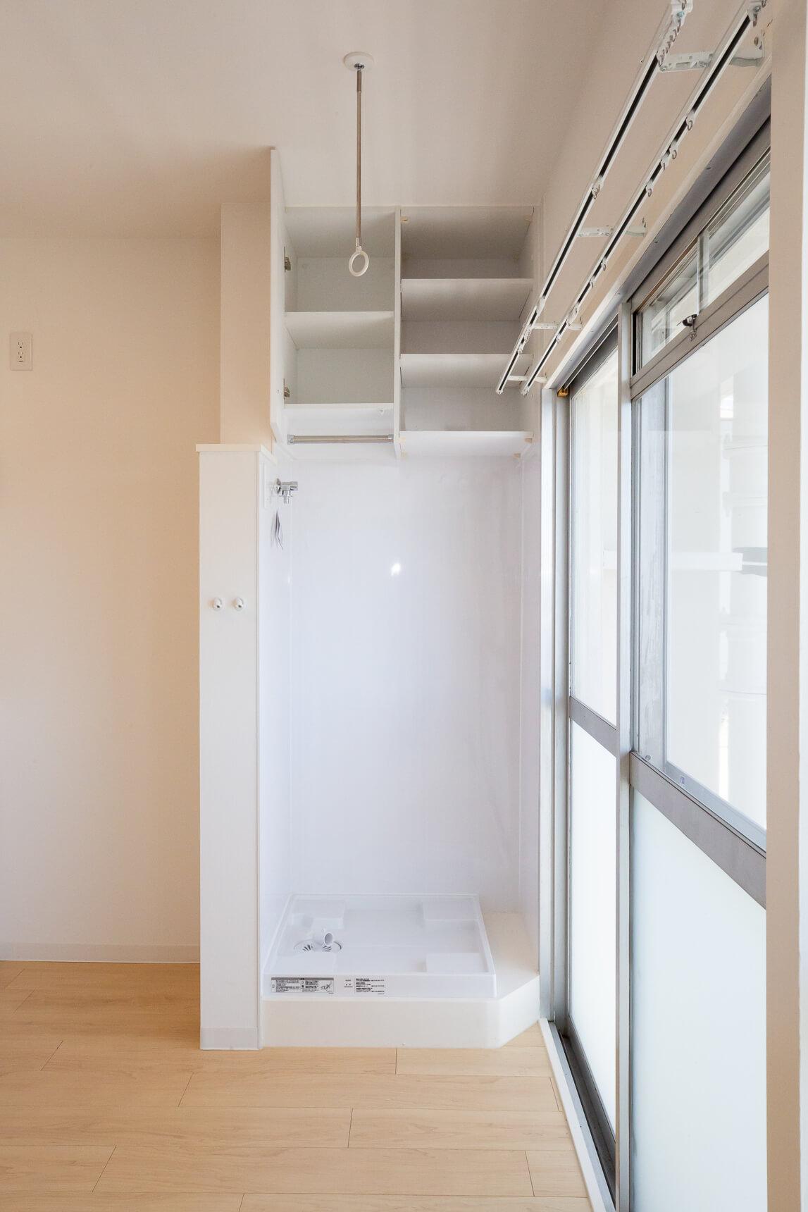 室内になかった洗濯機置き場は、ベランダの横に新設。すぐに洗濯物が干せるので便利ですね。取り外しも可能な、室内物干しポールもあり、上部は収納棚にもなっています。