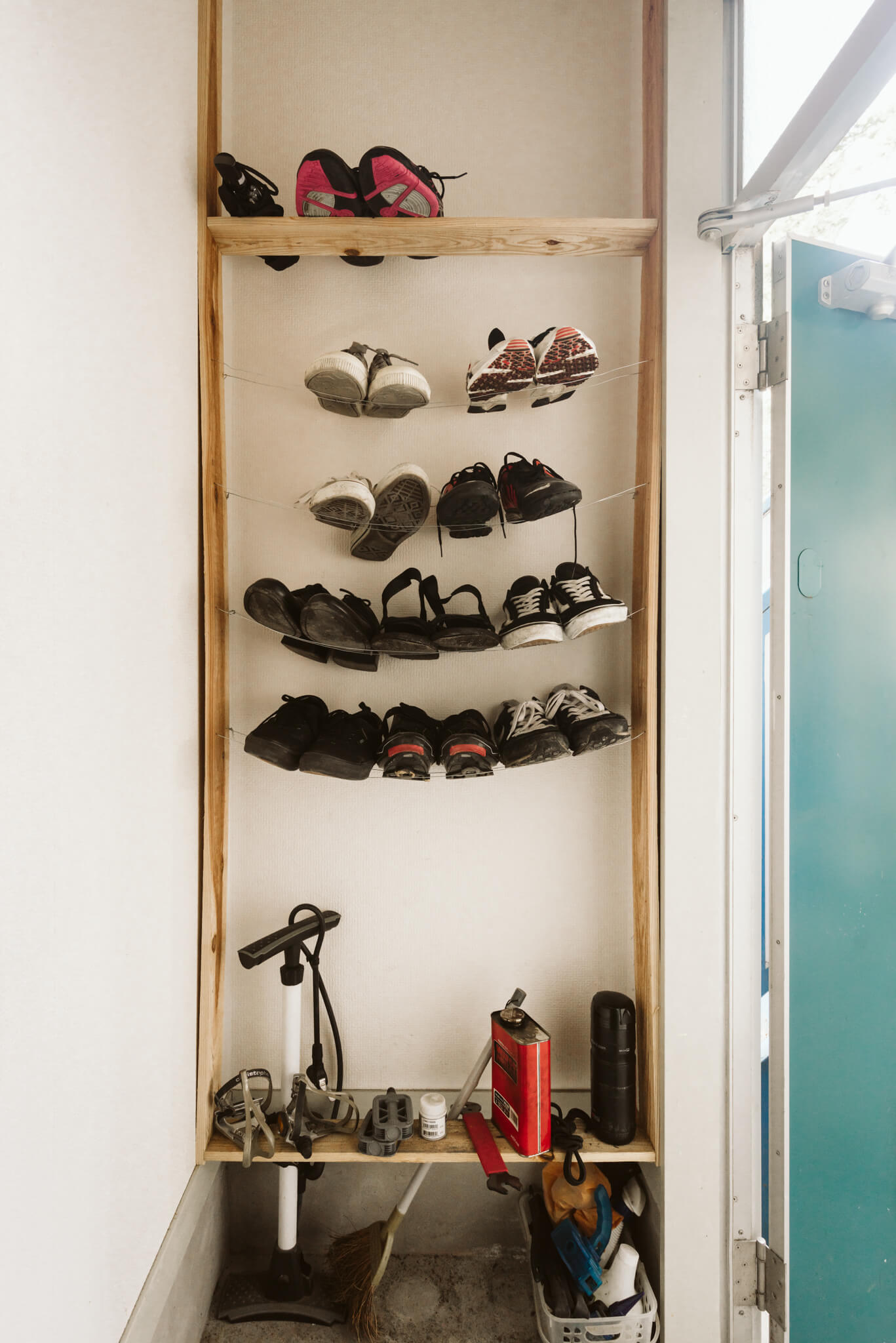 玄関には靴と趣味の自転車用品をしまう場所を。2本のワイヤーを棚板がわりにするアイディアで、空間が広く見えます。