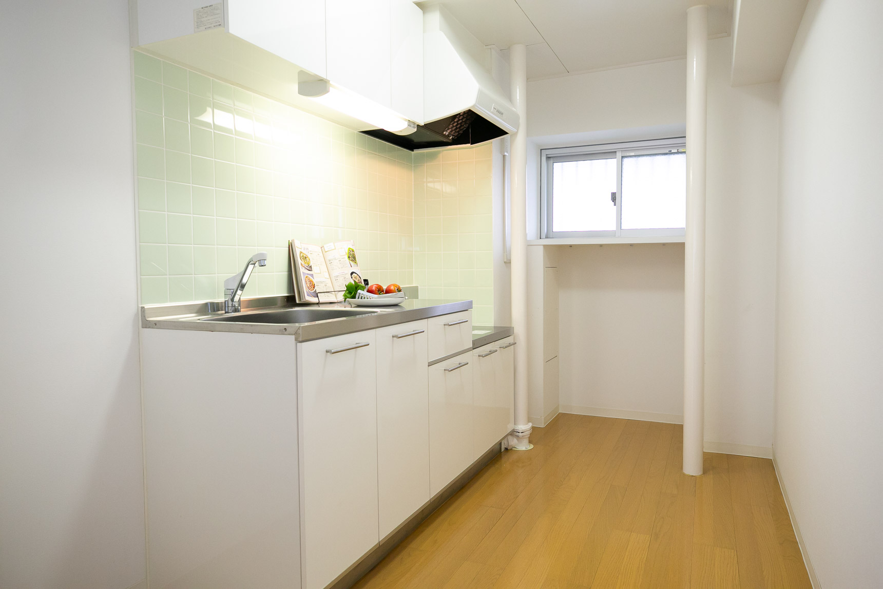 壁を新しく造作して大きな冷蔵庫も置けるように工夫されたキッチン。タイルは淡いグリーン、作業スペースも大きく、背面には好きなタイプの食器棚も置けそう。