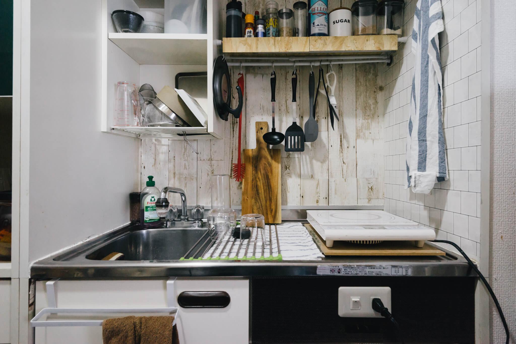 キッチンは、もともと付いていた棚と壁の間に突っ張り棒を2本取り付け、その上に板を置いて棚に。突っ張り棒には色々なものを引っ掛けることもでき、小さくても、しっかり自炊できるスペースになっています。