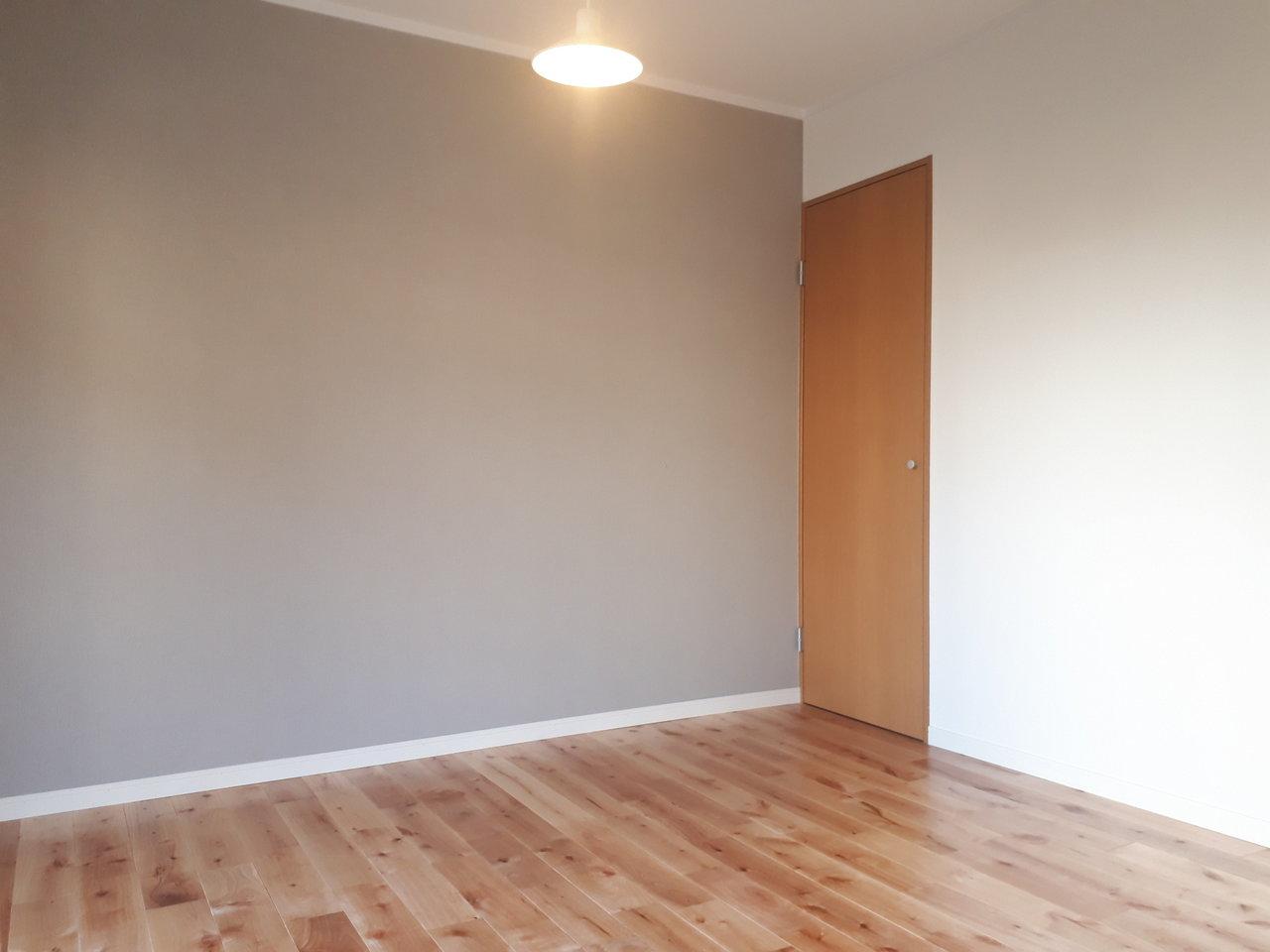 この物件の魅力は、なんといってもこのアクセントクロス。濃い色合いの無垢床と合う、深い灰色を選びました。