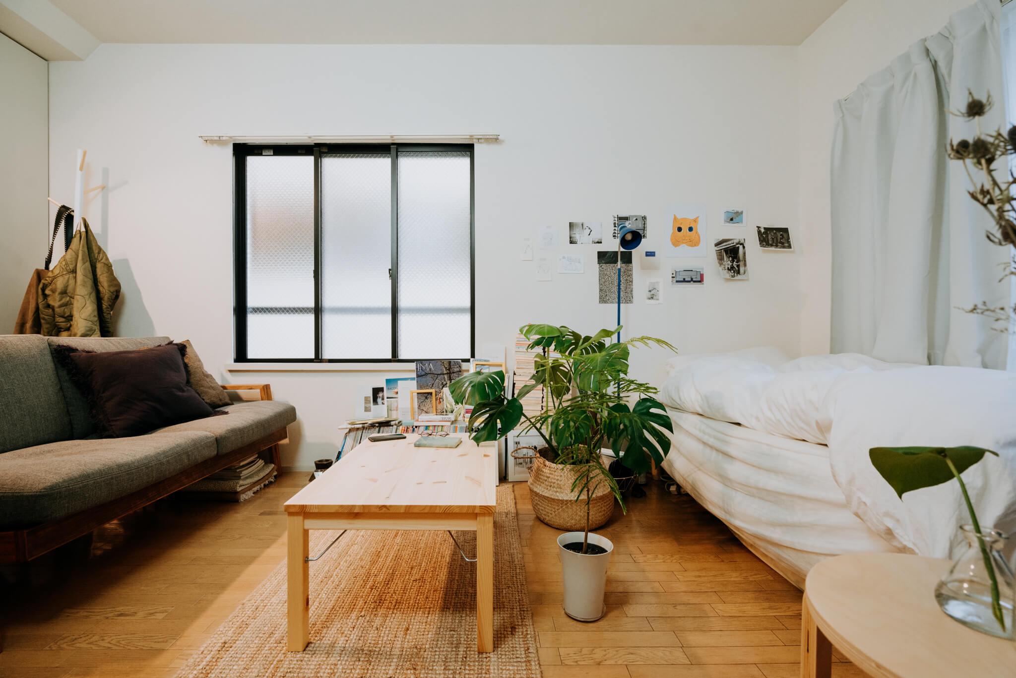 ベッドを窓側に寄せたことで、2シーターの大きなソファ、ローテーブルをおいてもゆとりのある空間に。ソファはリビングハウス、ローテーブルは無印良品の折りたためるタイプ。
