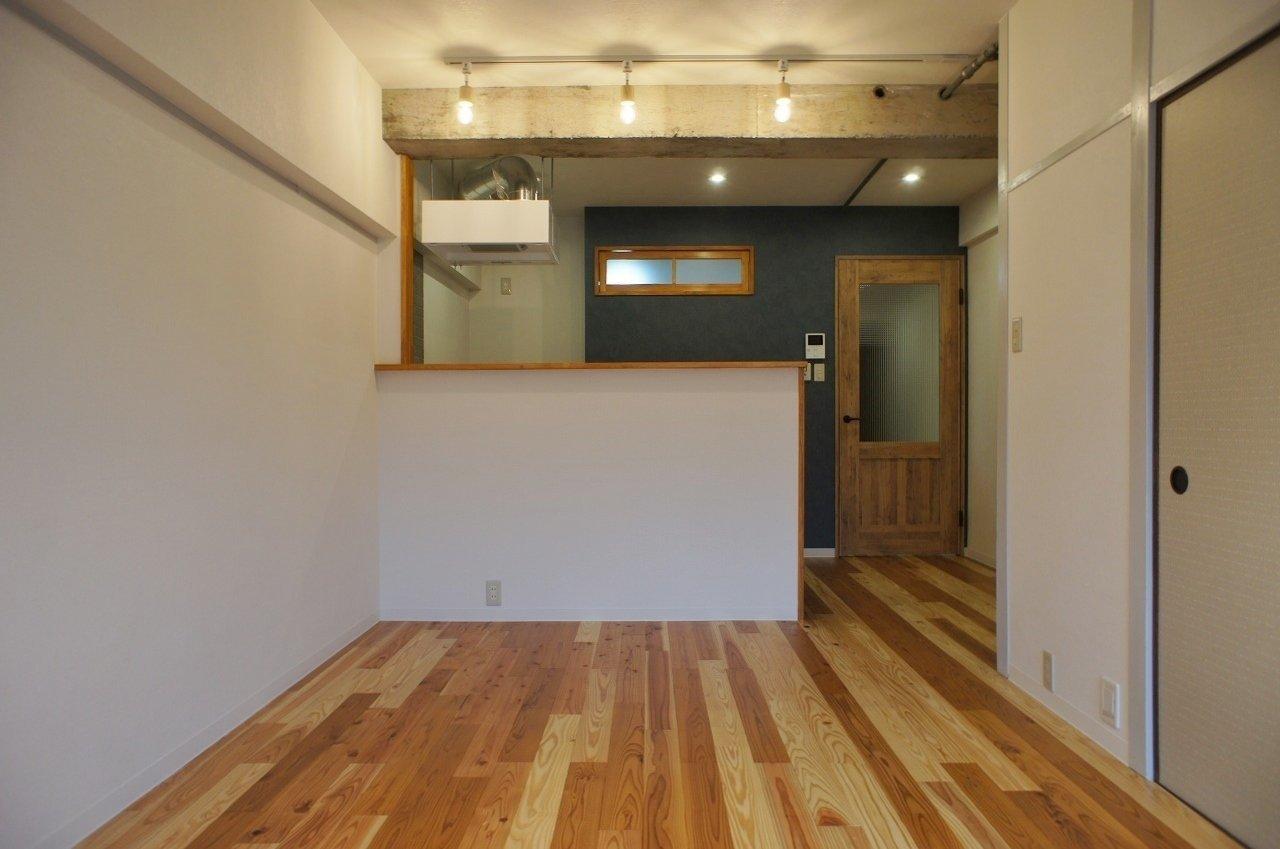 まるで雑誌に載っているカフェに来たかのような空間。濃い木材の色合いと、落ち着いた紺色の壁紙がマッチしています。背景に見える扉も、素敵な部屋の演出に一役買っていますね。おしゃれな暮らしに憧れる二人に、ぜひおすすめしたい物件です。