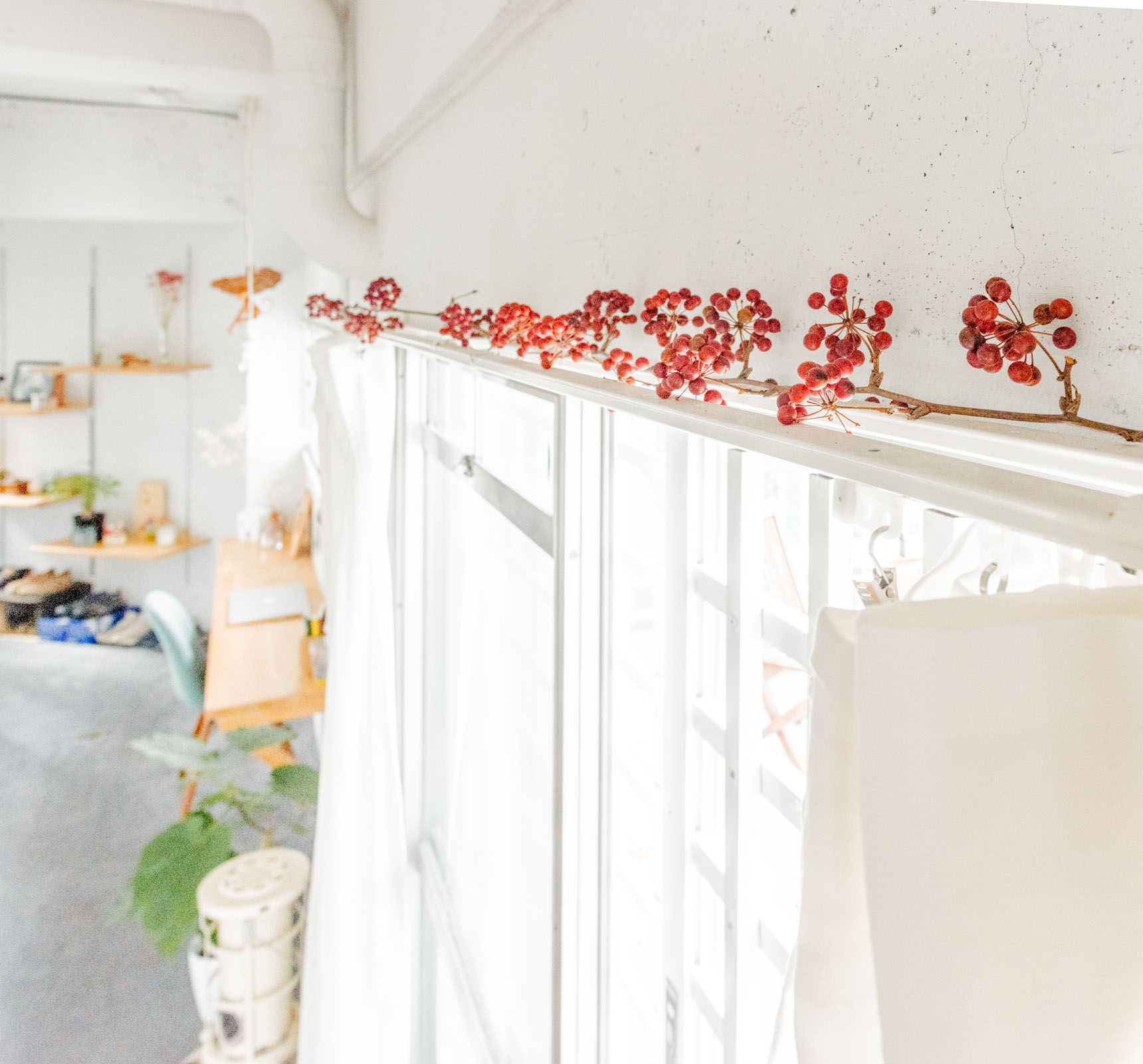 部屋のあちこちに置かれたオブジェやグリーンが素敵で、窓の上もこんな風に。全体的に白い内装に朱が映える。