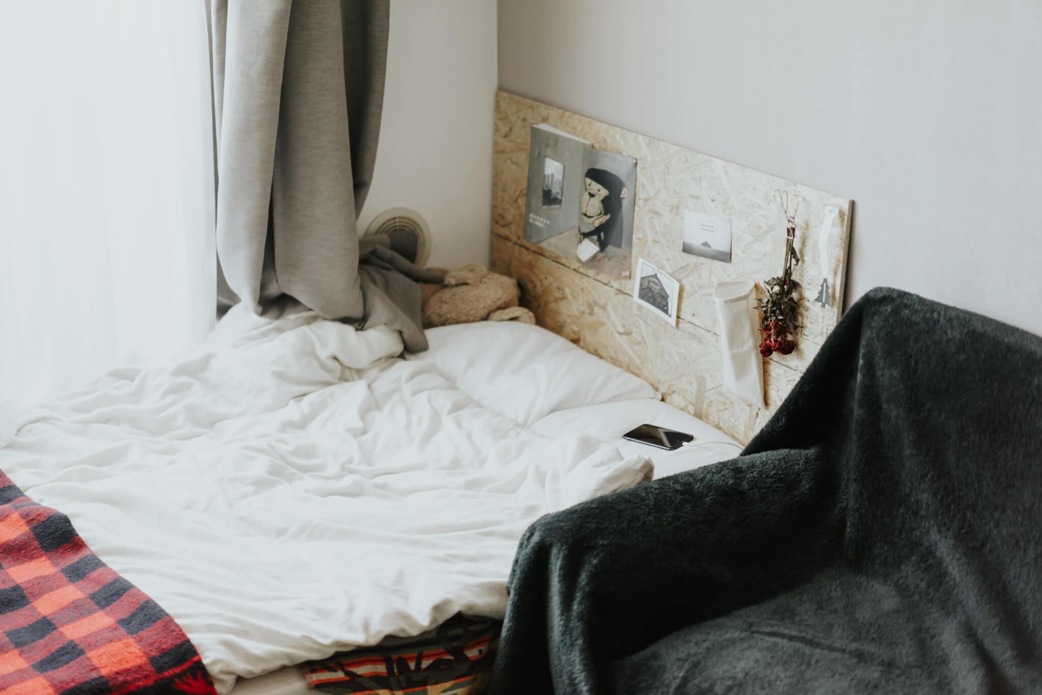 同じ合板を、ベッドのヘッドボード代わりに。
