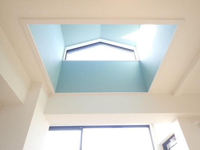 さて、もうひとつ目を見張るのは、リビングの天井部分。建物の最上階であるこちらのお部屋は、天井が高く、太陽の光が上から差し込む設計になっています。トップライトのブルーが部屋全体を爽やかに照らし出してくれるので、リビングでゆったりくつろげそうです。
