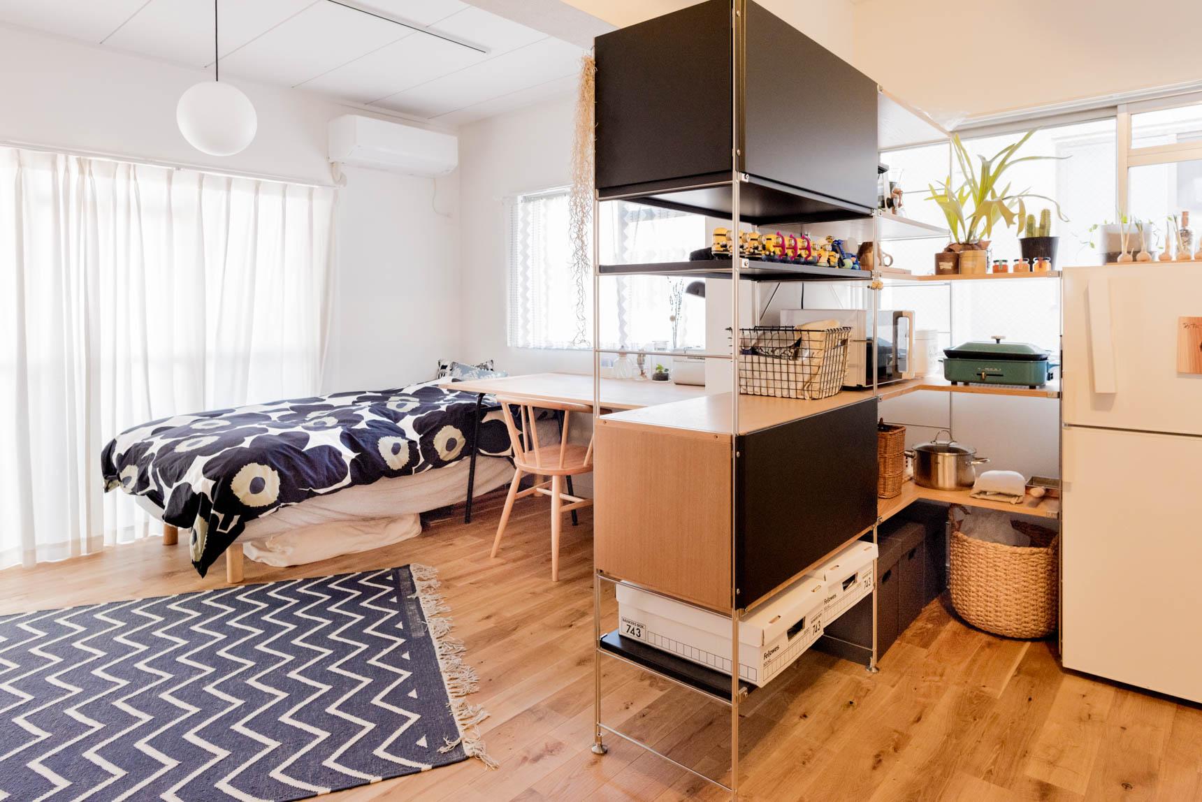 棚によって魅力的に仕切られたキッチンと居室。玄関からベッドは直線上にあるのだが、うまく仕切られている。それでいて完全に分断してはいない。とても巧みな仕切りだ。