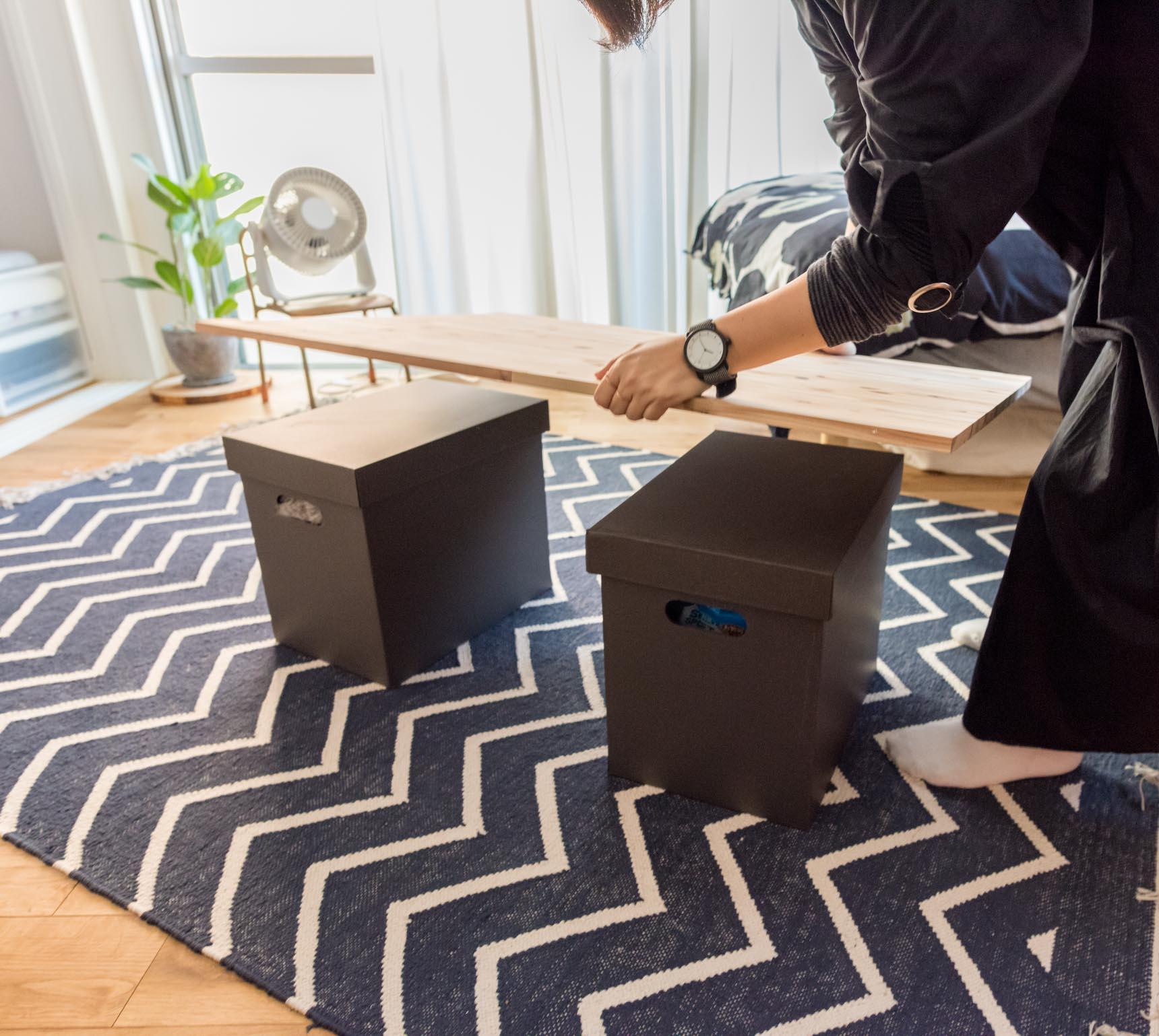 テーブルは友人が来たときなど、ひつような場面でセットする。脚は棚に入っていた箱。天板をのせてできあがり。斜めに敷かれたラグと共に良い空間を作っている。