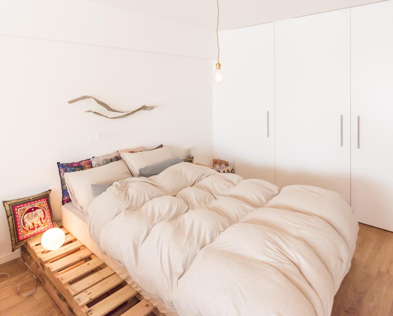 木製のパレットをベッドフレーム代わりに使うアイディア。あえてマットレスより大きめのサイズにすることでサイドテーブルも兼ねています。(このお部屋はこちら)