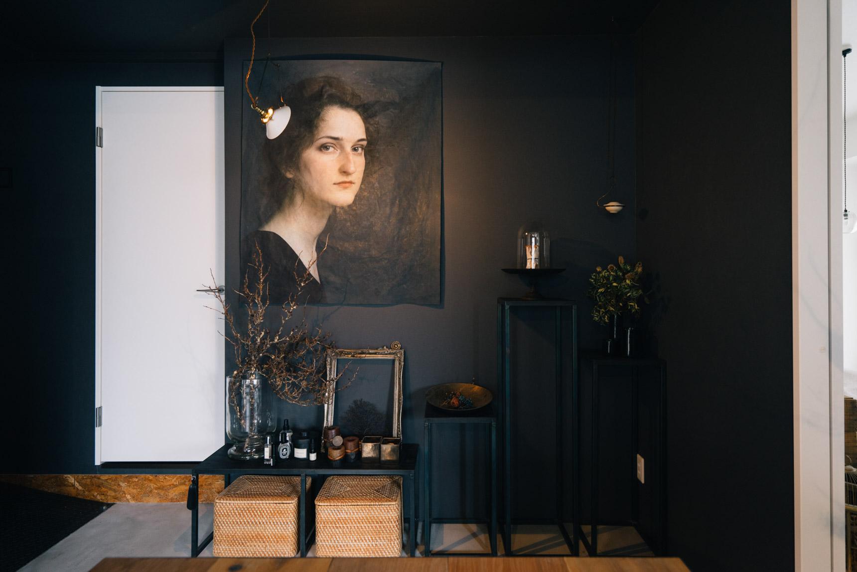 こちらのダイニングテーブル横の壁。キッチンと同じOSB合板だったのを、リビングと合わせた黒の壁紙にしてもらいました。かけられているのは、絵画を布にプリントし、さらにロウを塗りわざとシワをつけて仕上げた、オリジナルのアート。