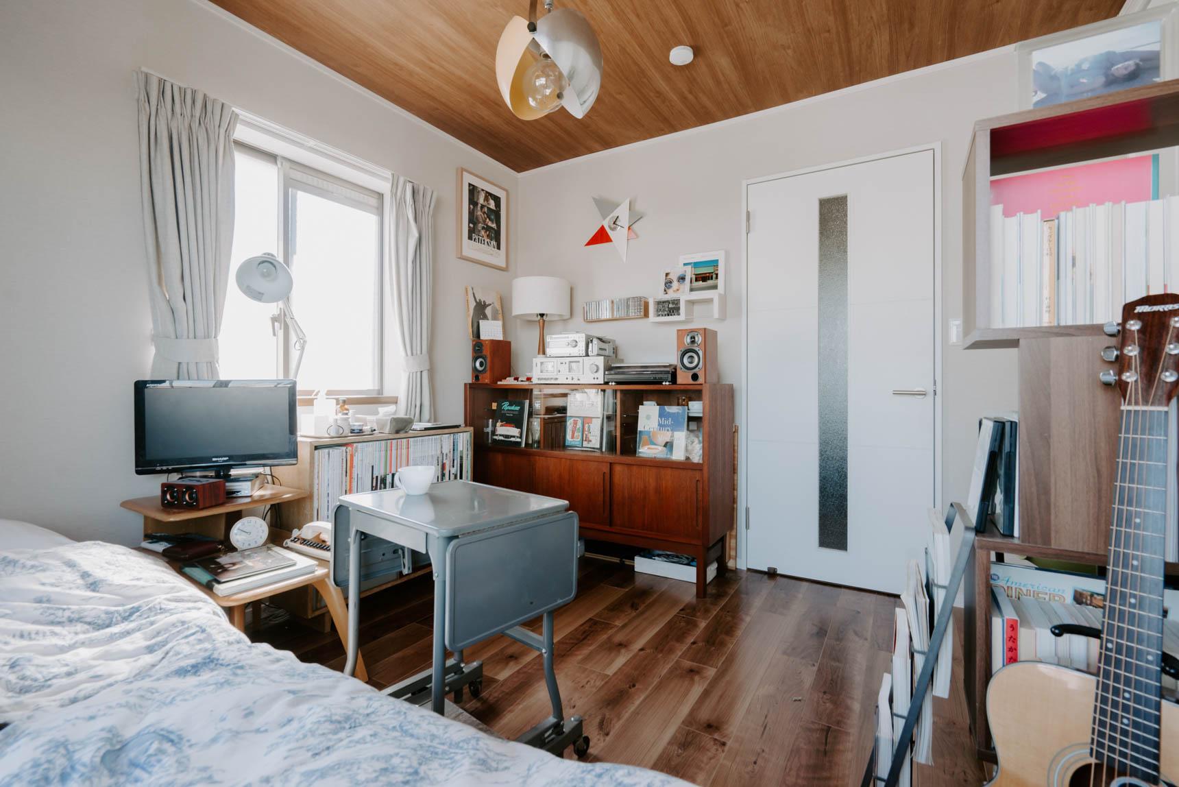 床と合わせて、天井もシックな木目調のワンルーム。それに合わせて、棚やサイドテーブルも少し濃い木目のものが揃っています。