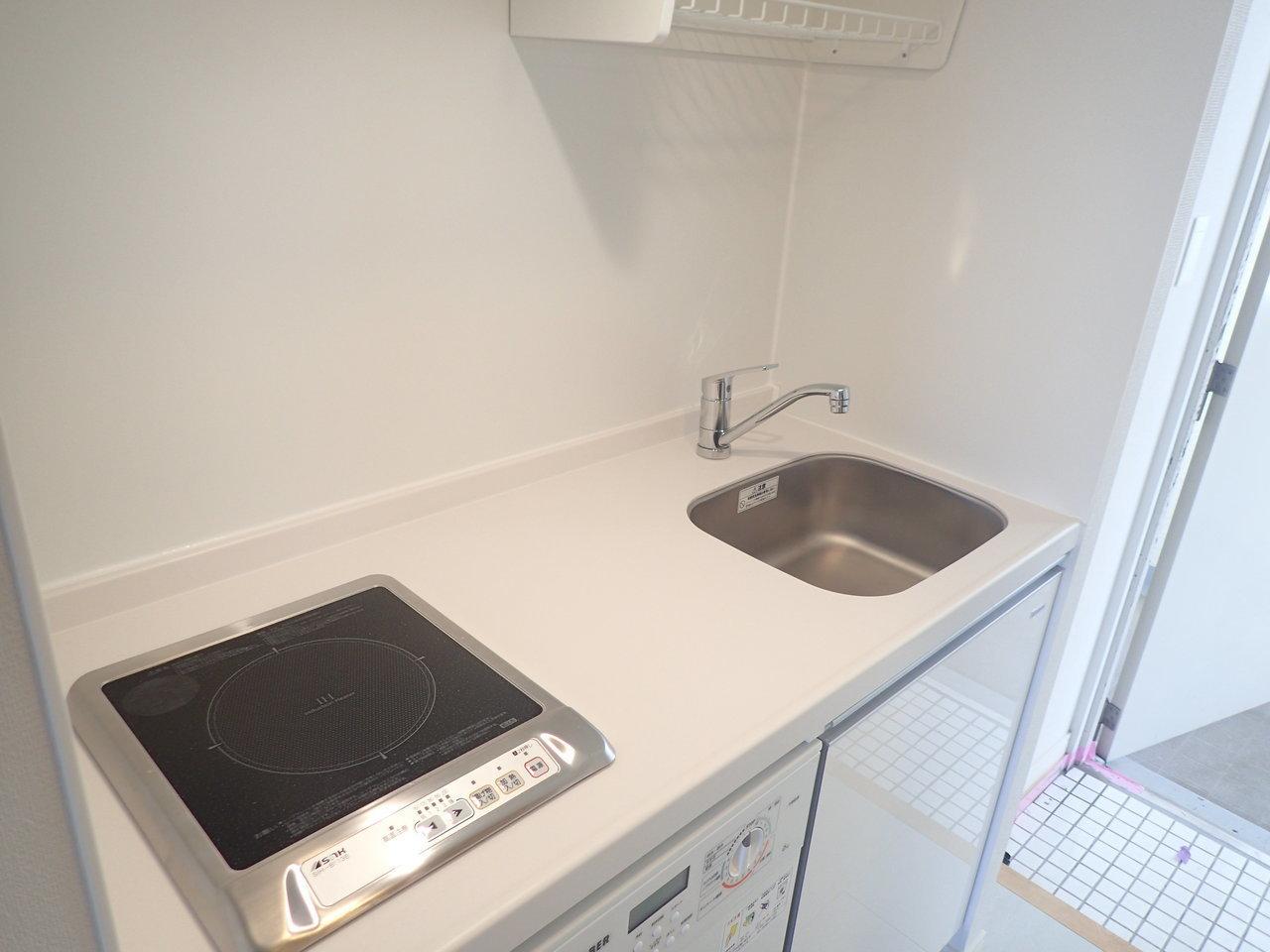 キッチンはシンプル。シンクの上には吊り棚がついているので、洗い物を置いたり、フックをかけて調理器具を収納したりしてもいいですね。