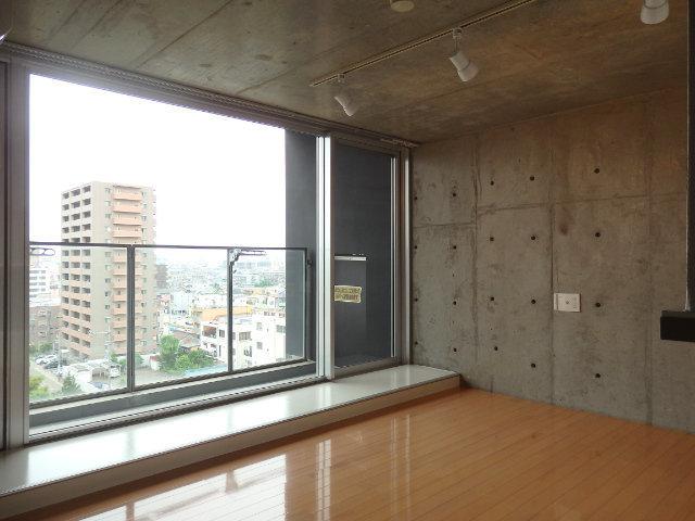 居室には大きな窓とベランダが。コンクリ打ちっぱなしの仕上げになっています。壁にはビスなどを打ち込んで、ひっかけるインテリア、なんてアレンジもできそう。