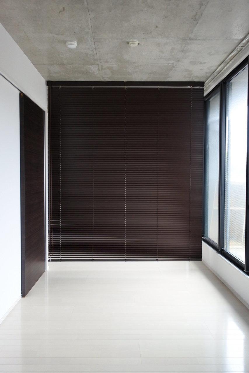 高めの天井はコンクリ打ちっぱなし。ブラインドで洋室とLDKを仕切ります。
