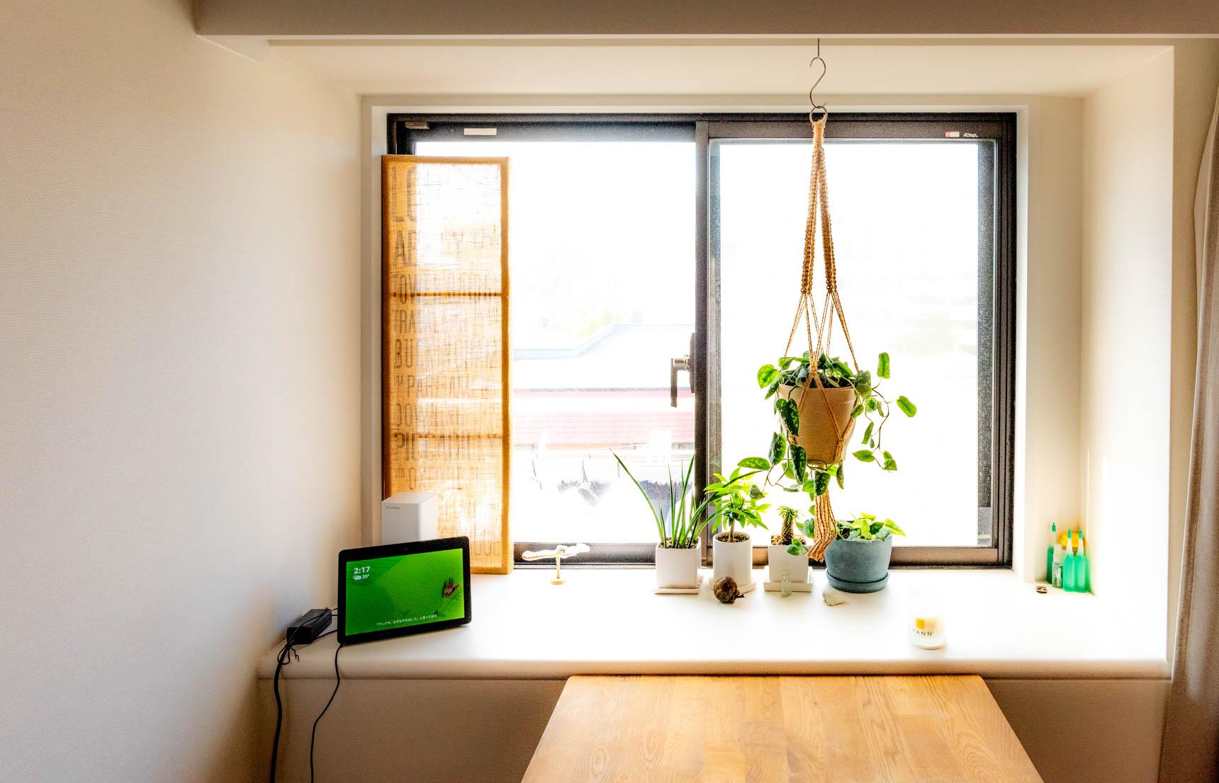 キッチンの真向かい、ちょっと変わった位置にある出窓。広い縁があるそこをすてきに使っている。ここにもグリーンがたくさん。