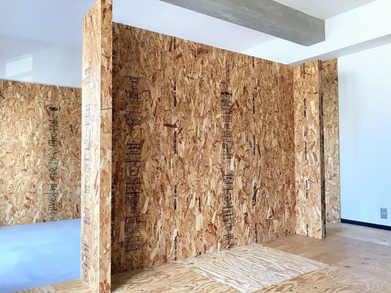 パーティクルボードの壁がすごい存在感を放つ、リノベーションのお部屋です。