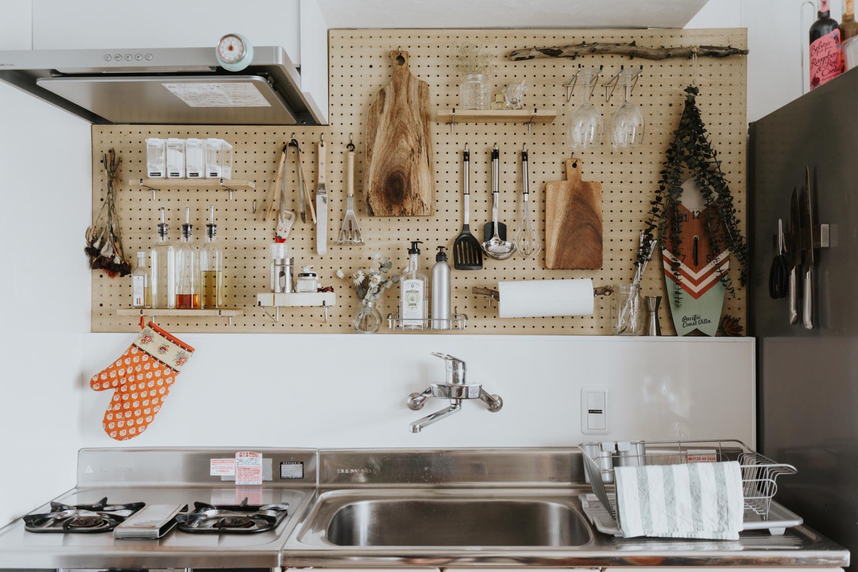 ちょっとレトロで味のあるキッチンは、吊り戸棚などの収納が一切ついていなかったのを逆手にとって、ディアウォールを使って有孔ボードを貼り、壁面収納を作りました。キッチンに有孔ボードって、すごくいいですね。