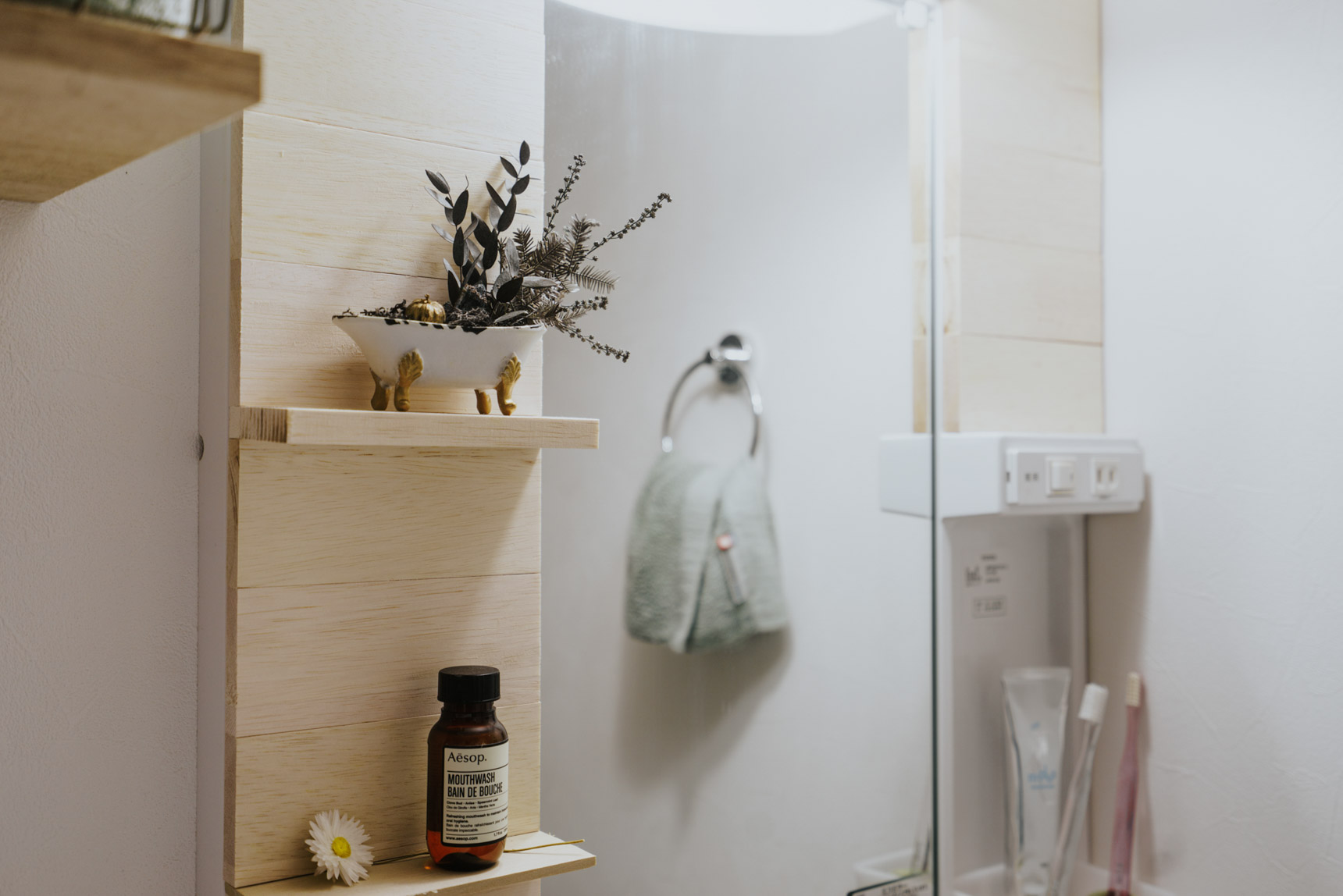 賃貸のお部屋でぜひ取り入れたいな、と思ったのは、よくある洗面台に木材を貼り付けて雰囲気をよくするテクニック。板を挟み込むことで、ちょっとした棚も作られていました。これは素敵。