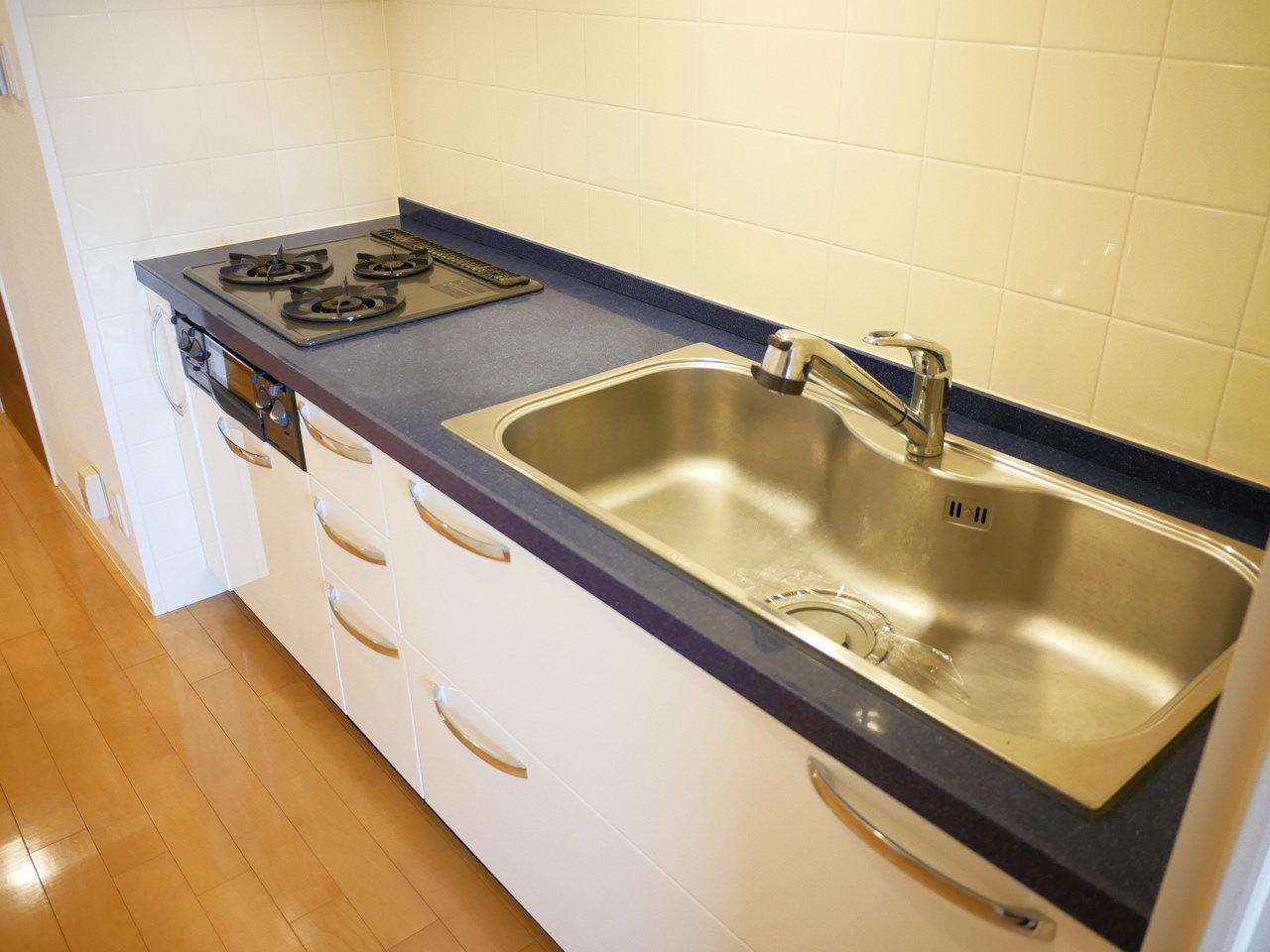 廊下にあるキッチンはネイビーとホワイトの2トーン!取手のディテールもよく見るとおしゃれです。1人暮らし向けのお部屋にしてはワイドサイズなので、自炊が自然と楽しくできそうですね。