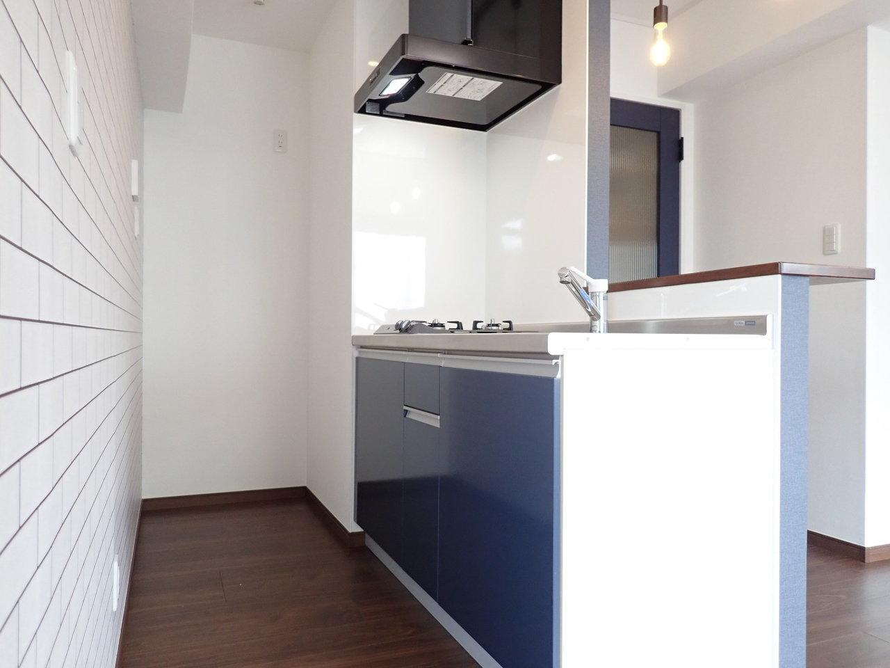 コンロは二口あり、さらに背面のスペースは広くとってあります。奥には冷蔵庫。背面には食器や炊飯器などを置いておける棚をDIYしてもいいかも。