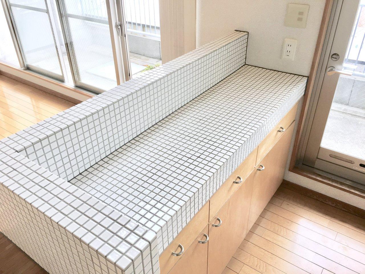 タイル貼りされたキッチンカウンターは、家電スペースがしっかりあります。こんなキッチンだったらコーヒーだって豆から挽いて淹れたくなります……。もちろん調理スペースもしっかりあるシンクも広々。コンロは2口です。