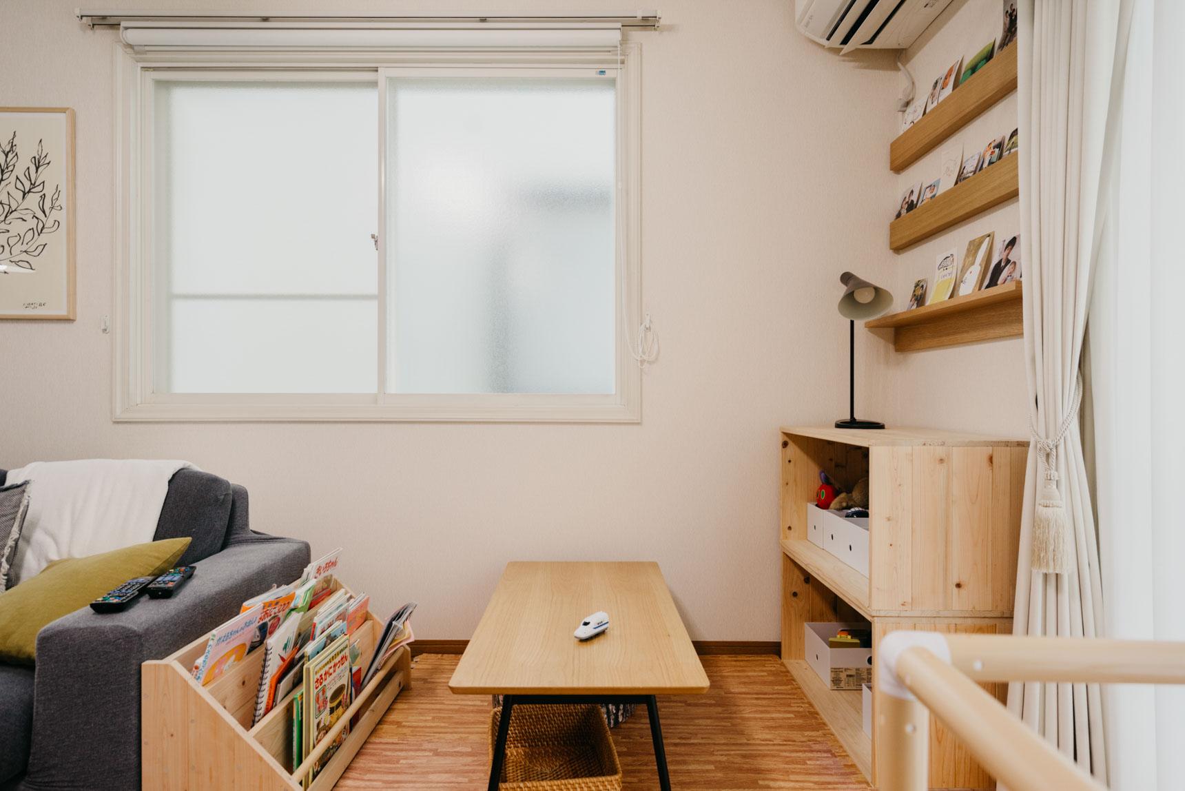 カラフルな絵本の入った本棚は、リビングの入口からは目に入らない位置に。その向かいには、息子さんのおもちゃと、家族の写真を飾るスペースが。