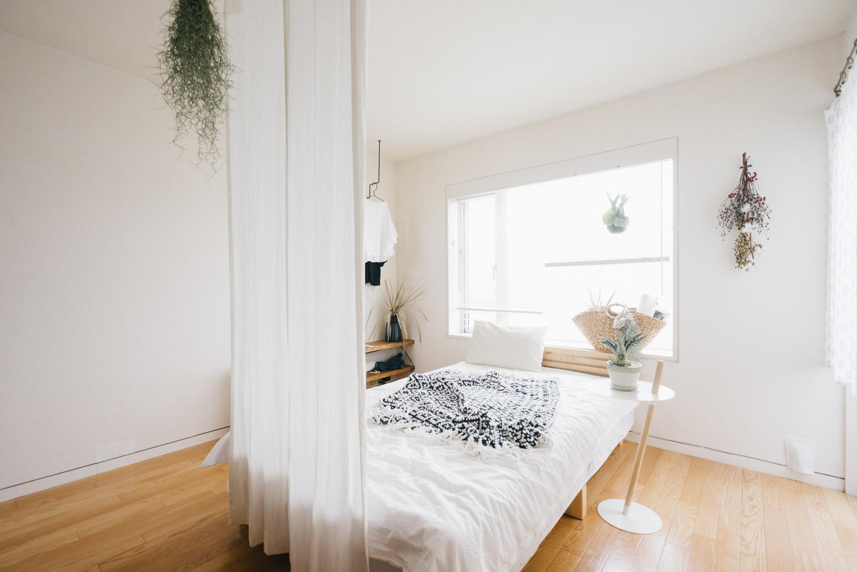 縦に長いワンルーム、寝室とリビングとは、天井から布をさげてゆるく仕切ります。「窓からの光を遮らないように、両サイドは開けるように工夫しています」